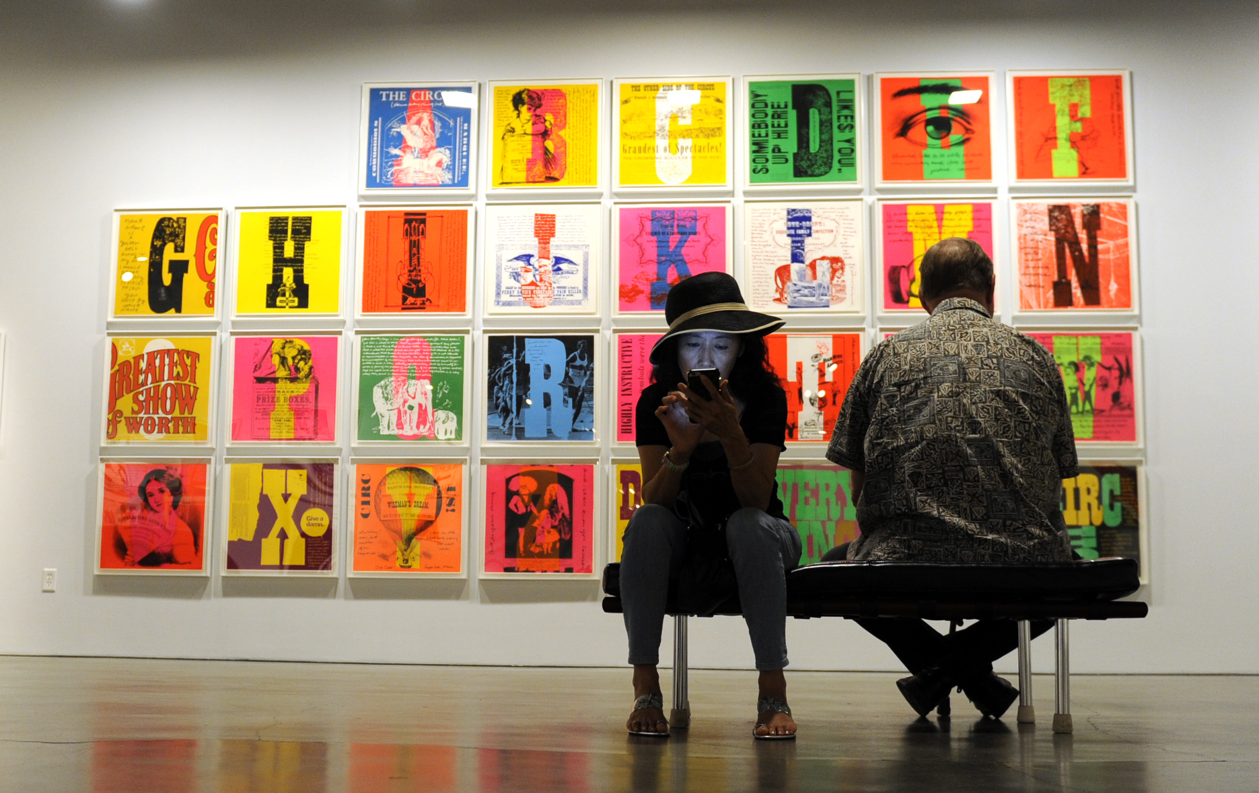 """Glory Huang, left, looks at her phone during a docent tour of """"Someday is Now: The Art of Corita Kent"""" at the Pasadena Museum of California Art on Saturday, July 11, 2015 in Pasadena, Calif."""