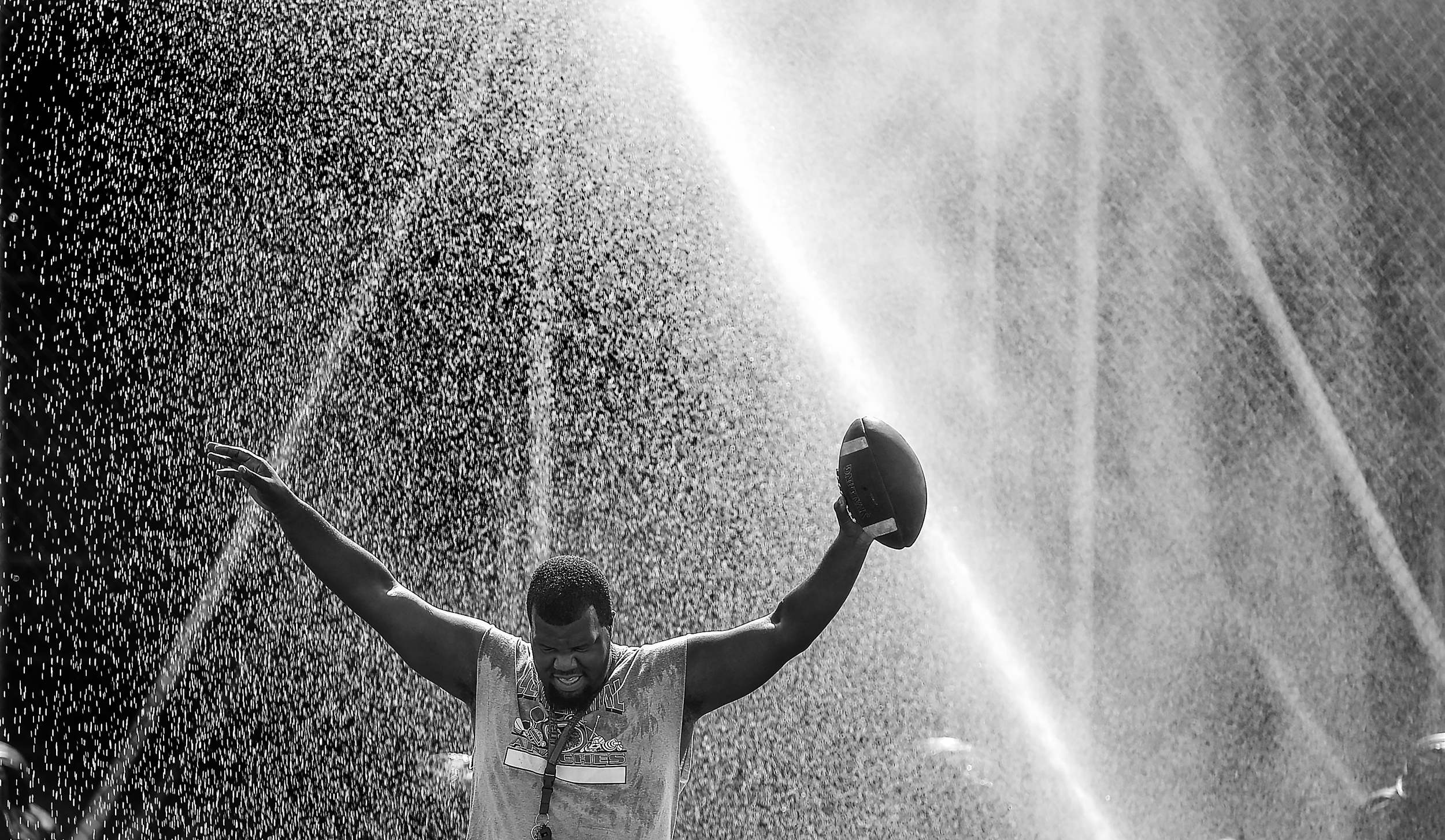 Coach Djon Low takes advantage of a water sprinkler to cool off during a summer football practice at Centennial High School in Compton, CA. Wednesday July 29, 2015.