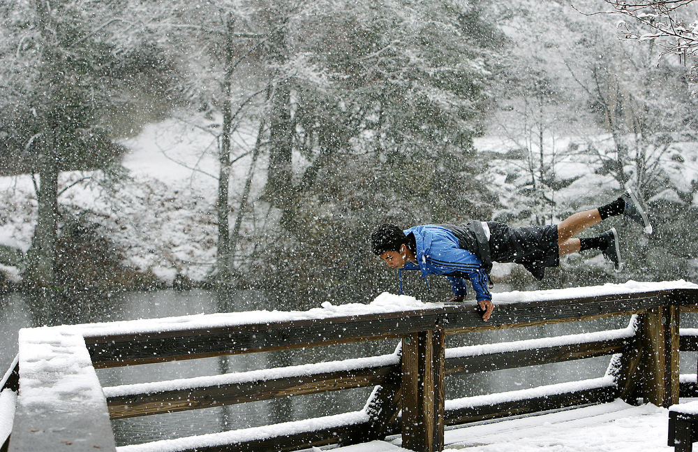 Jessy March,16, of Palm Springs shows off for friends with a hand stand on the deck of Lake Fulmor above the ice cold water as snow falls at the 5,000ft. level in the San Bernardino National Forest Sunday near Idyllwild, CA. March 1, 2015.