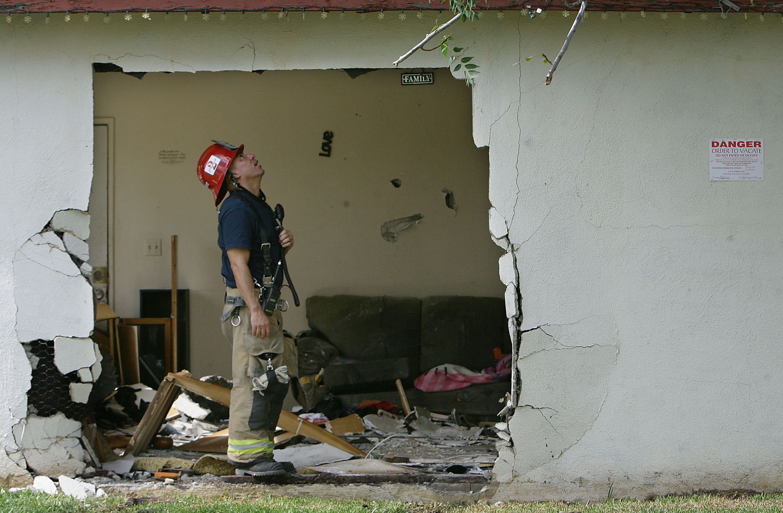 Moreno Valley Fire Station 2 fire Captain Michael Martinez looks over the damage after a pickup truck hit a parked pickup truck and plowed in to a home trapping woman between the couch and the truck Thursday in Moreno Valley, August 6, 2015.