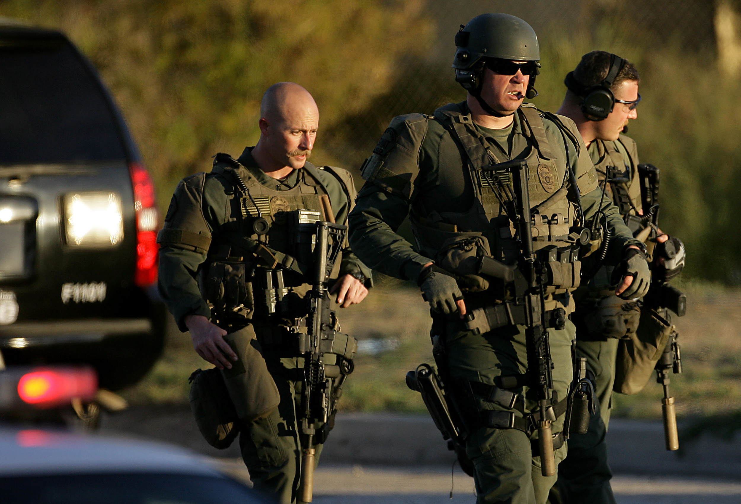 Police officers leave the scene as after one or two of the gunmen were shot and killed in a gun battle on San Bernardino Avenue east of Richardson Street after killing 14 people and shooting  14 more during a mass shooting in San Bernardino Wednesday, Dec. 2, 2015.
