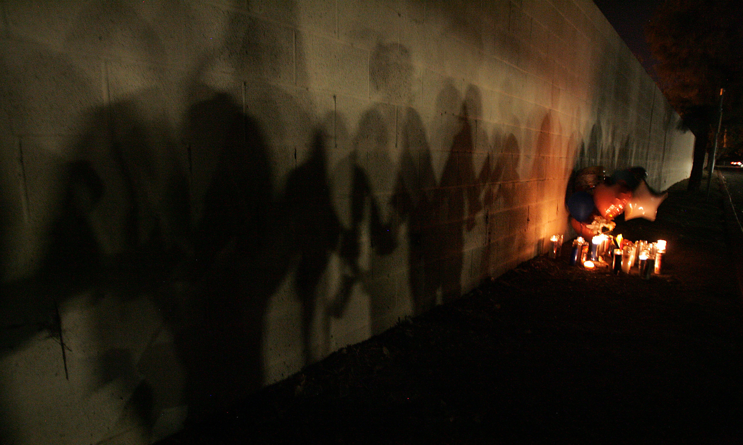 THe shadows of family and friends as they hold a candle light vigil for Isaac Kelly, 33, who was shot and killed by a security guard just after midnight in an apartment complex in the 150 block of E. Nuevo Road Saturday in Perris, CA. October 3, 2015.