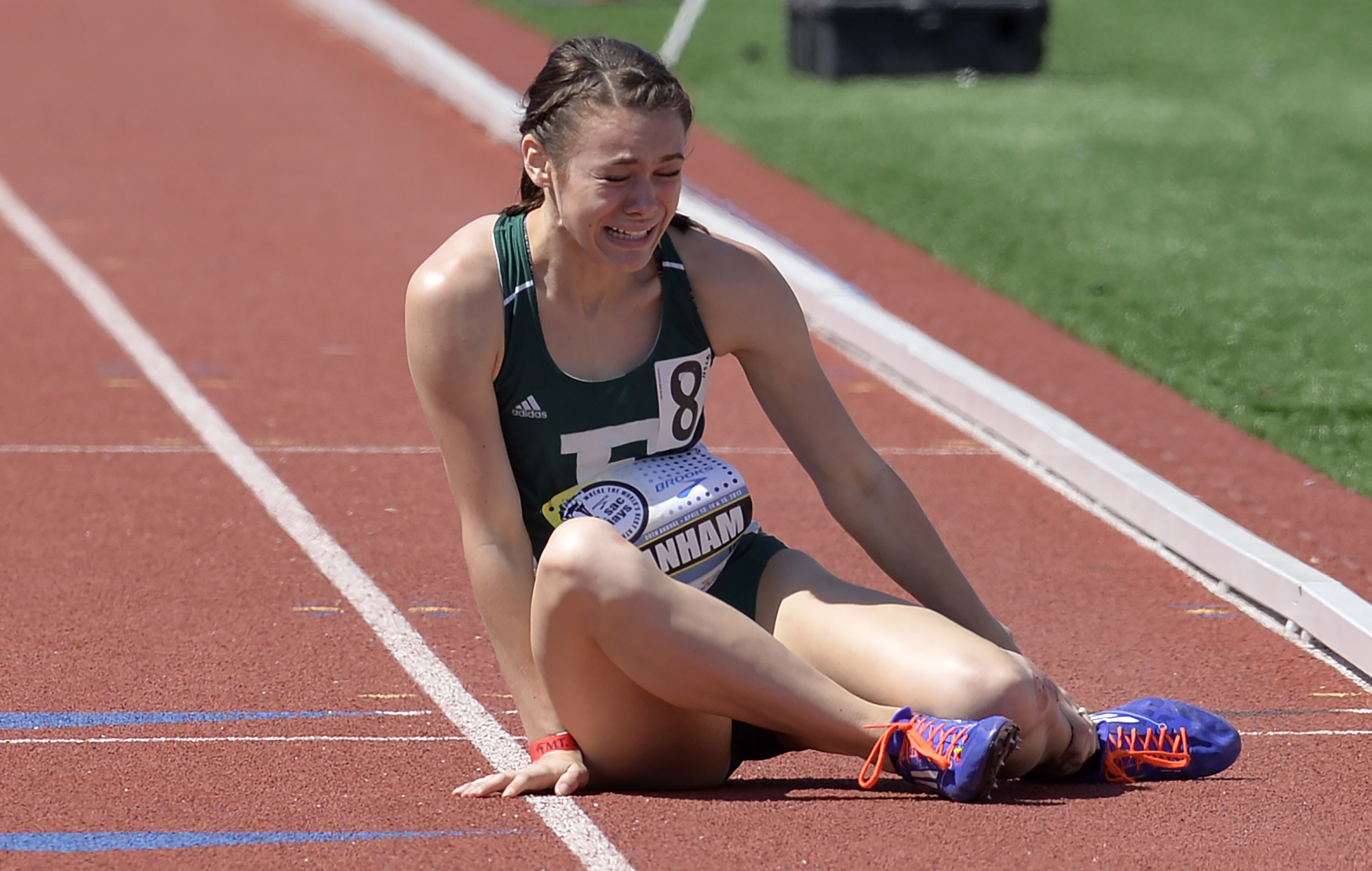 Rebekah Branham, of Eastern Michigan, lies on the track holding her injured ankle after stumbling in the 800m College Open Section 3  event at the Mt. SAC Relays at are El Camino College in Torrance Friday, April 14, 2017.