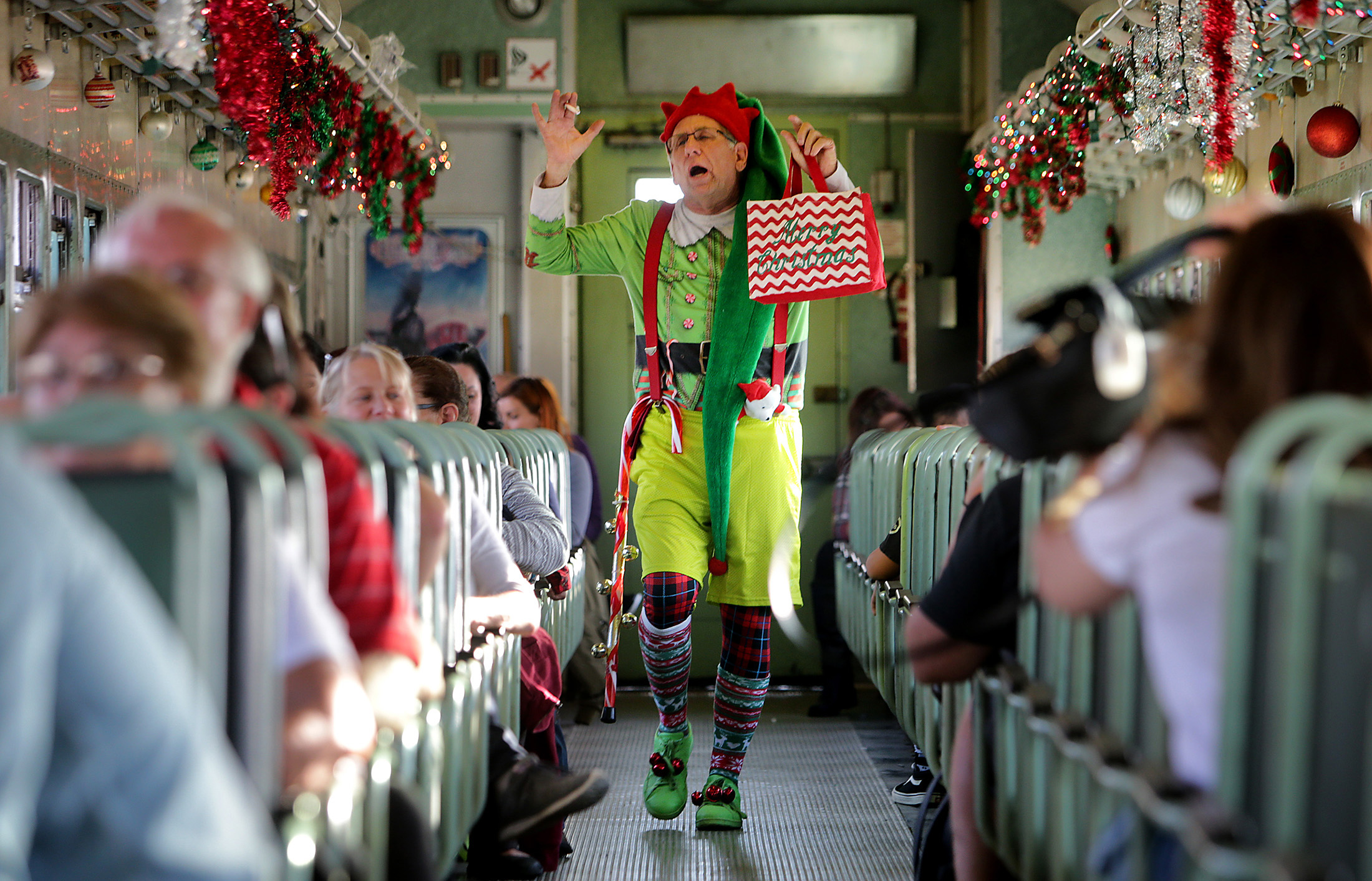 "Ken Schwartz plays Jingles the elf as he sings and dances for guests on the train during ""Take a Train to Santa's Workshop"" at Orange Empire Railway Museum Sunday in Perris, CA. December 3, 2017."