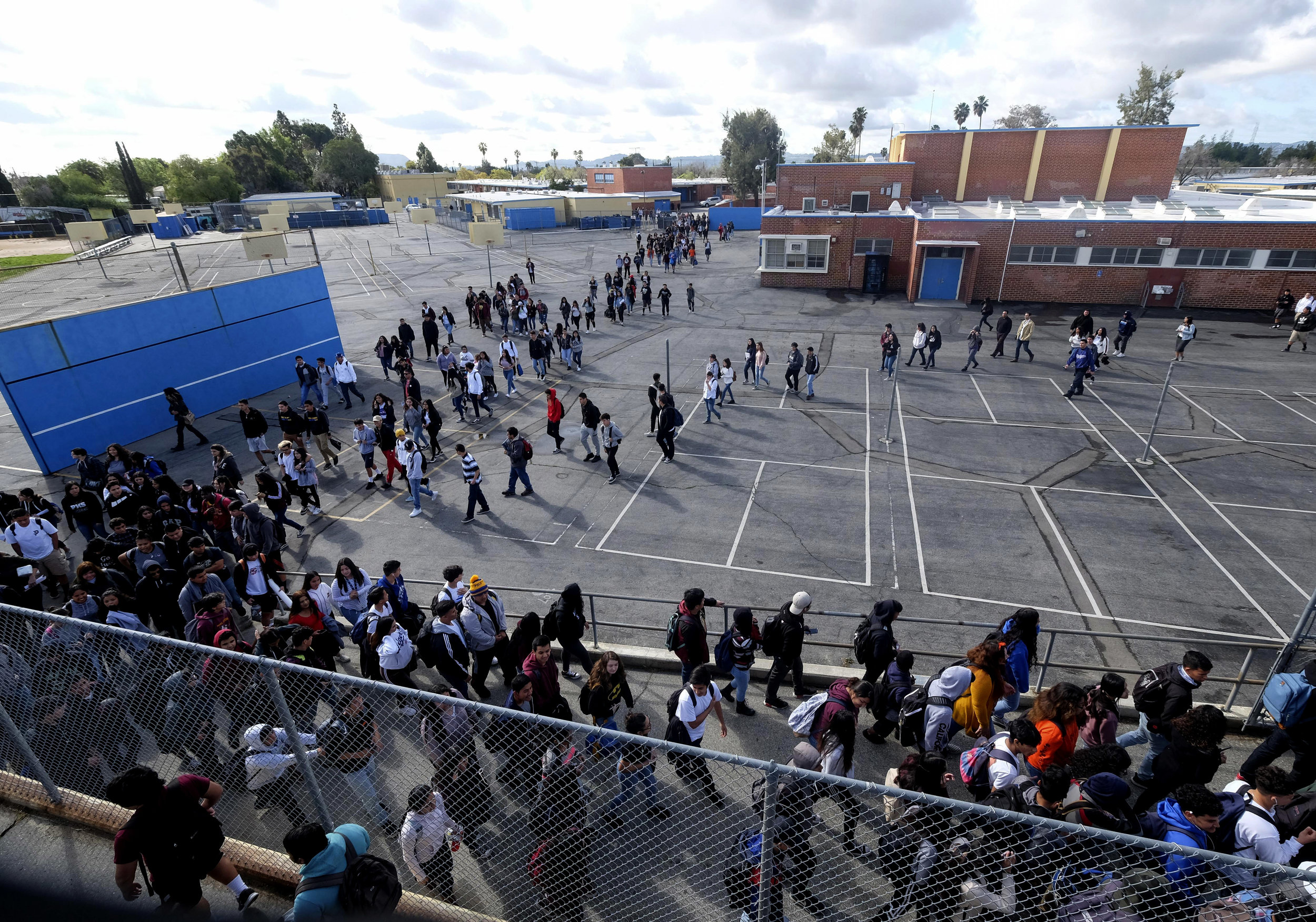 Students from Francis Polytechnic High School walk out their campus for ``#NeverAgain,'' an assembly which spotlights the meaning of school safety for students as part of a nationwide protest against gun violence, Wednesday, March 14, 2018, in Los Angeles.