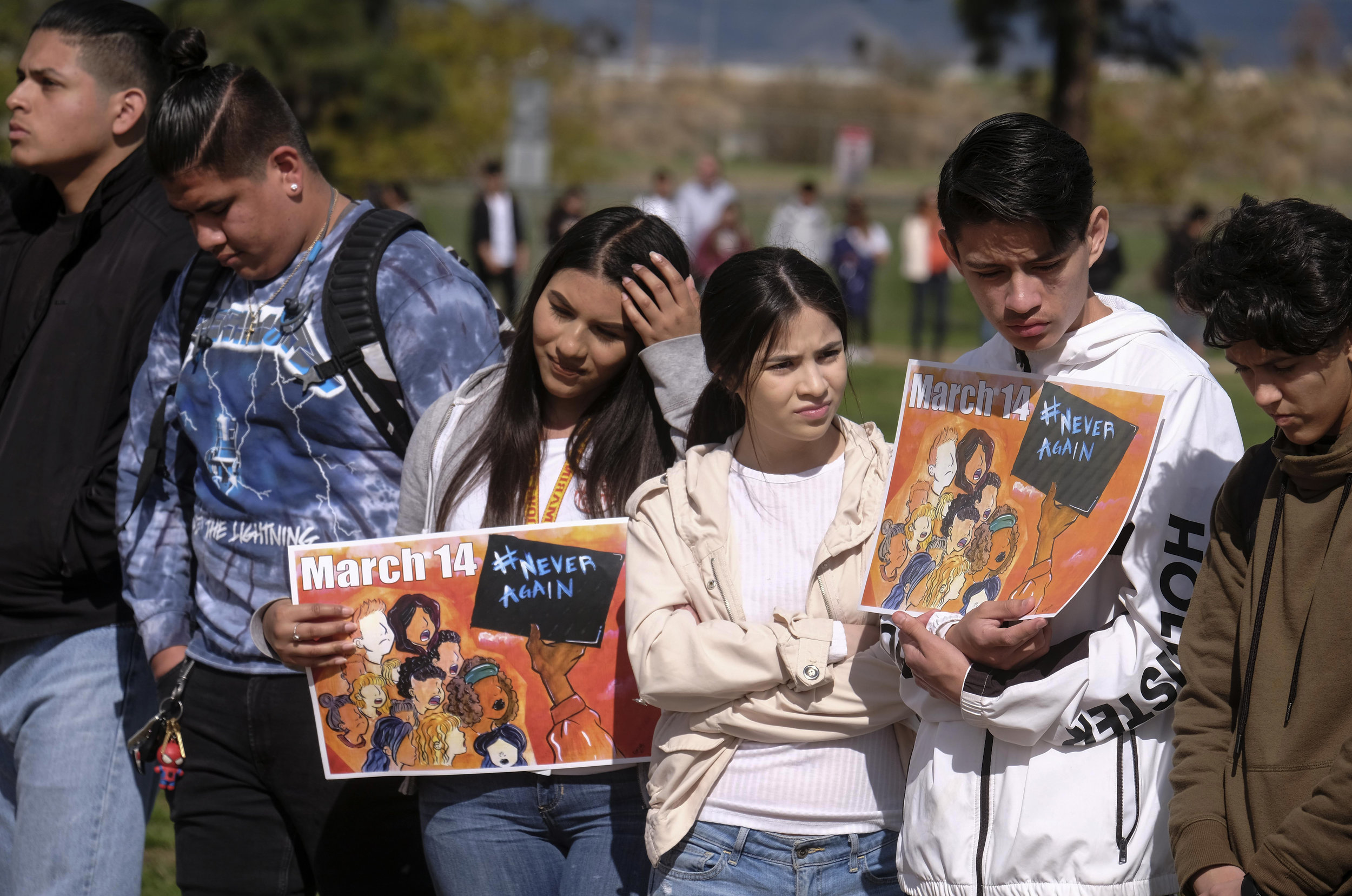 Students from Francis Polytechnic High School hold up signs during ``#NeverAgain,'' an assembly which spotlights the meaning of school safety for students as part of a nationwide protest against gun violence, Wednesday, March 14, 2018, in Los Angeles.