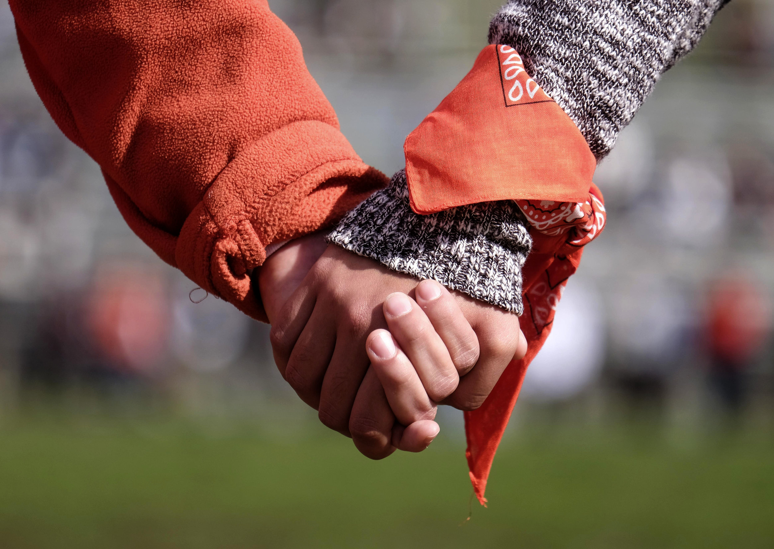 Students from Francis Polytechnic High School link arms on their football field for ``#NeverAgain,'' an assembly which spotlights the meaning of school safety for students as part of a nationwide protest against gun violence, Wednesday, March 14, 2018, in Los Angeles.