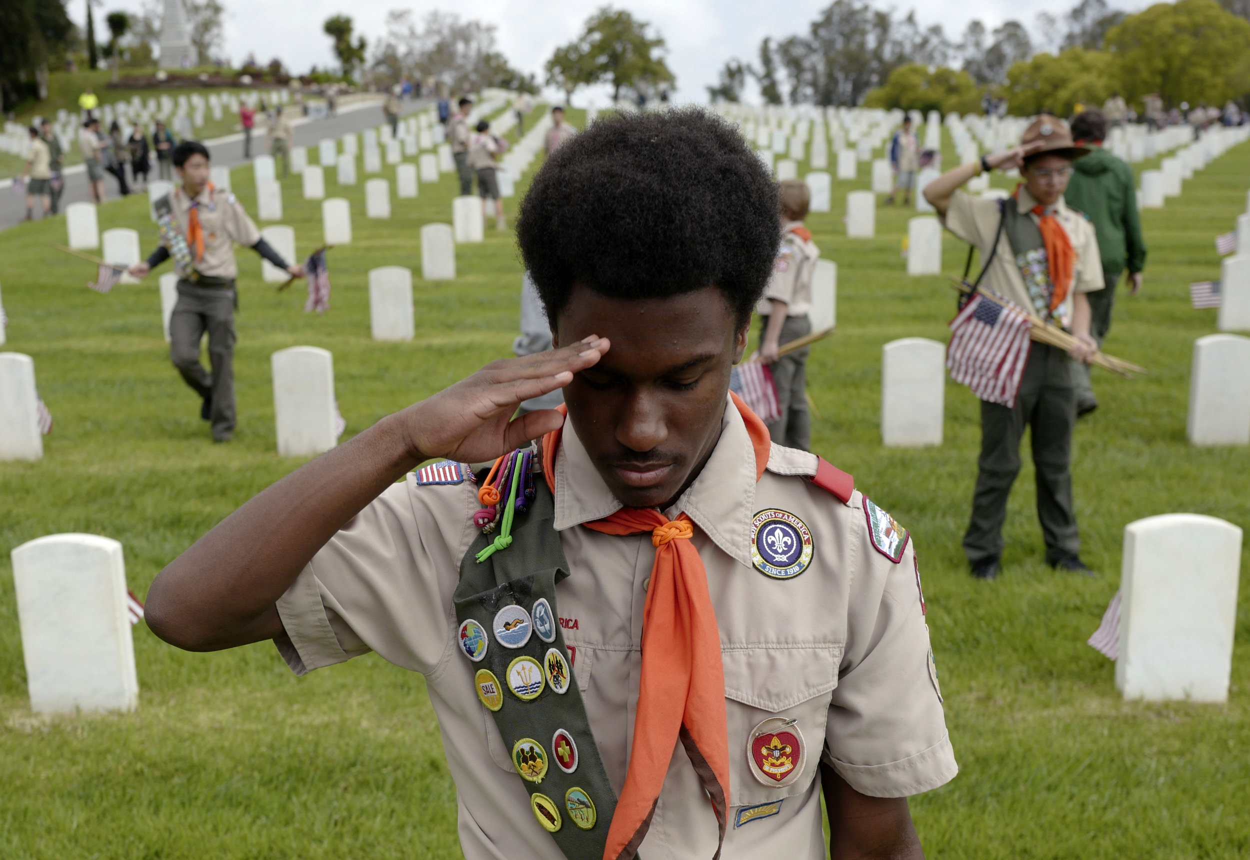 A boy scout salutes after placing a U.S. flag in front of a grave stone at Los Angeles National Cemetery Saturday, May 26, 2018, for the Memorial Day celebrations in Los Angeles.