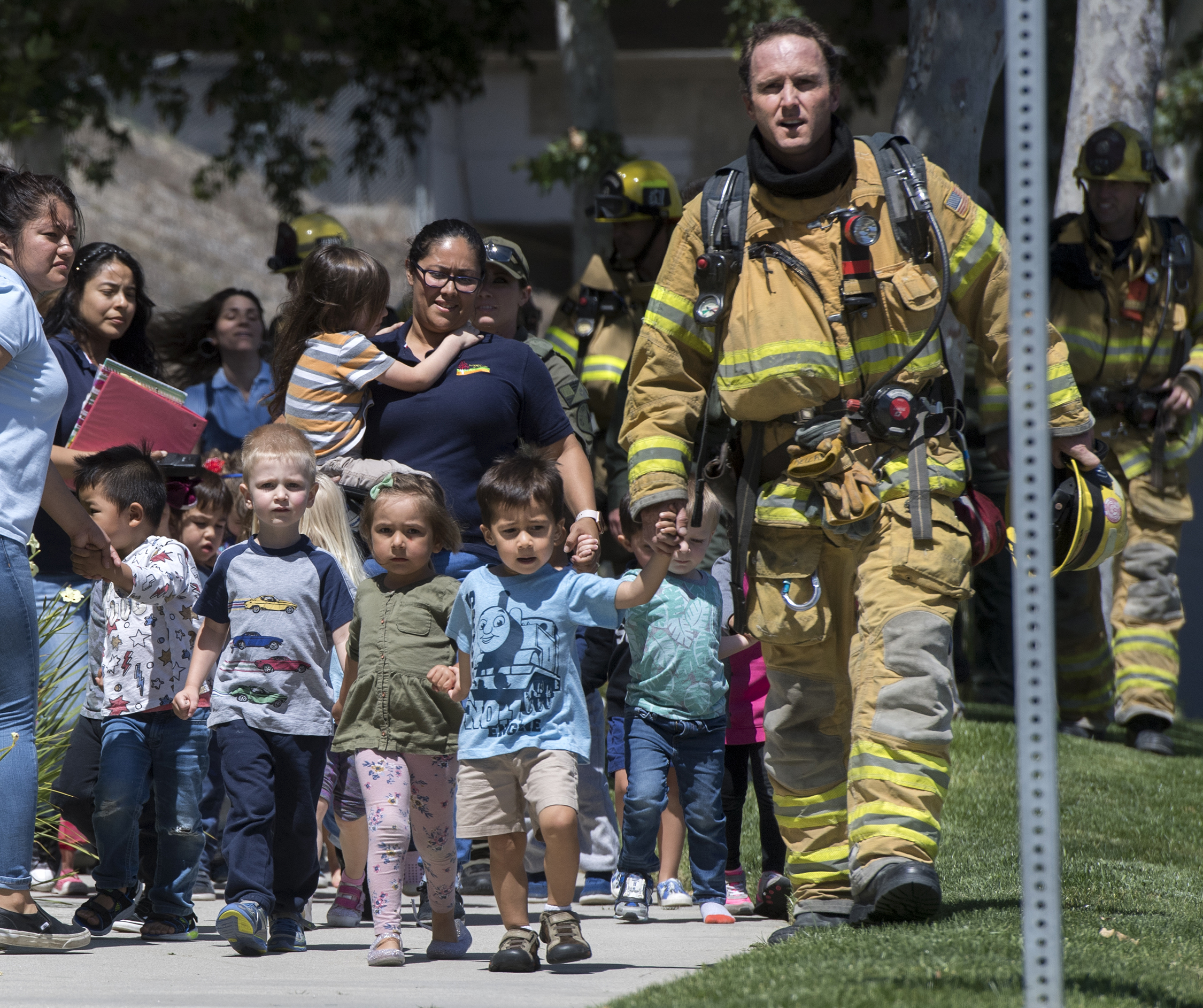 Fire fighters and Sheriff deputies escort children from Academy on the Hill pre-k school in Aliso Viejo on Tuesday, May 15, 2018 after a nearby explosion killed one person and injured two others.