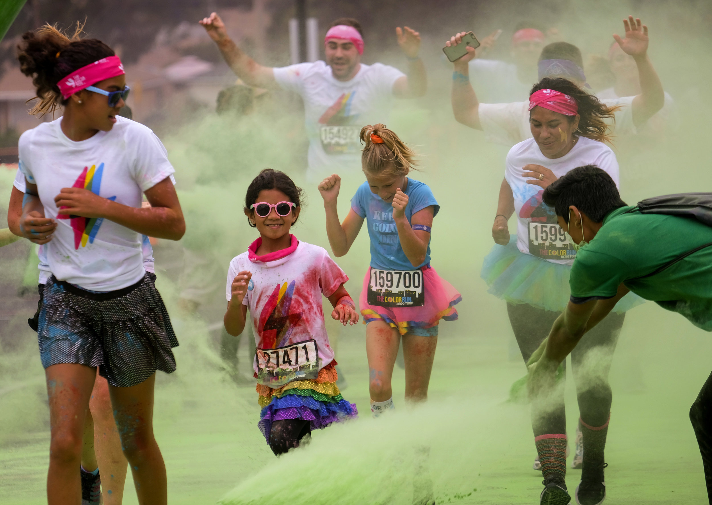 Runners revel while running through clouds of colorful powder thrown by volunteers in the Color Run at the StubHub Center in Los Angeles, United States, June 23, 2018.