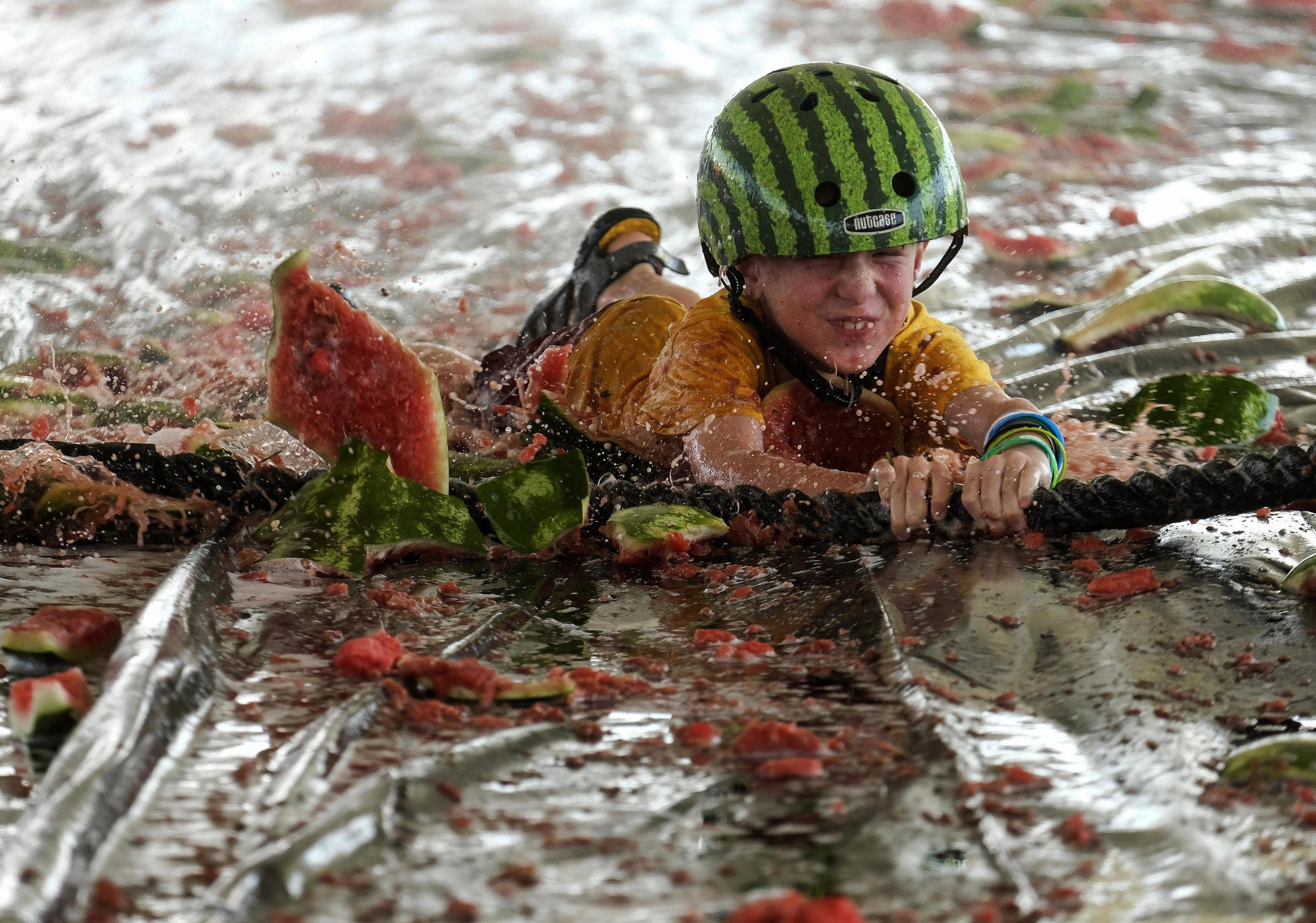 A boy plays melon skiing at the 56th Annual California Watermelon Festival in Los Angeles, Saturday, July 28, 2018.