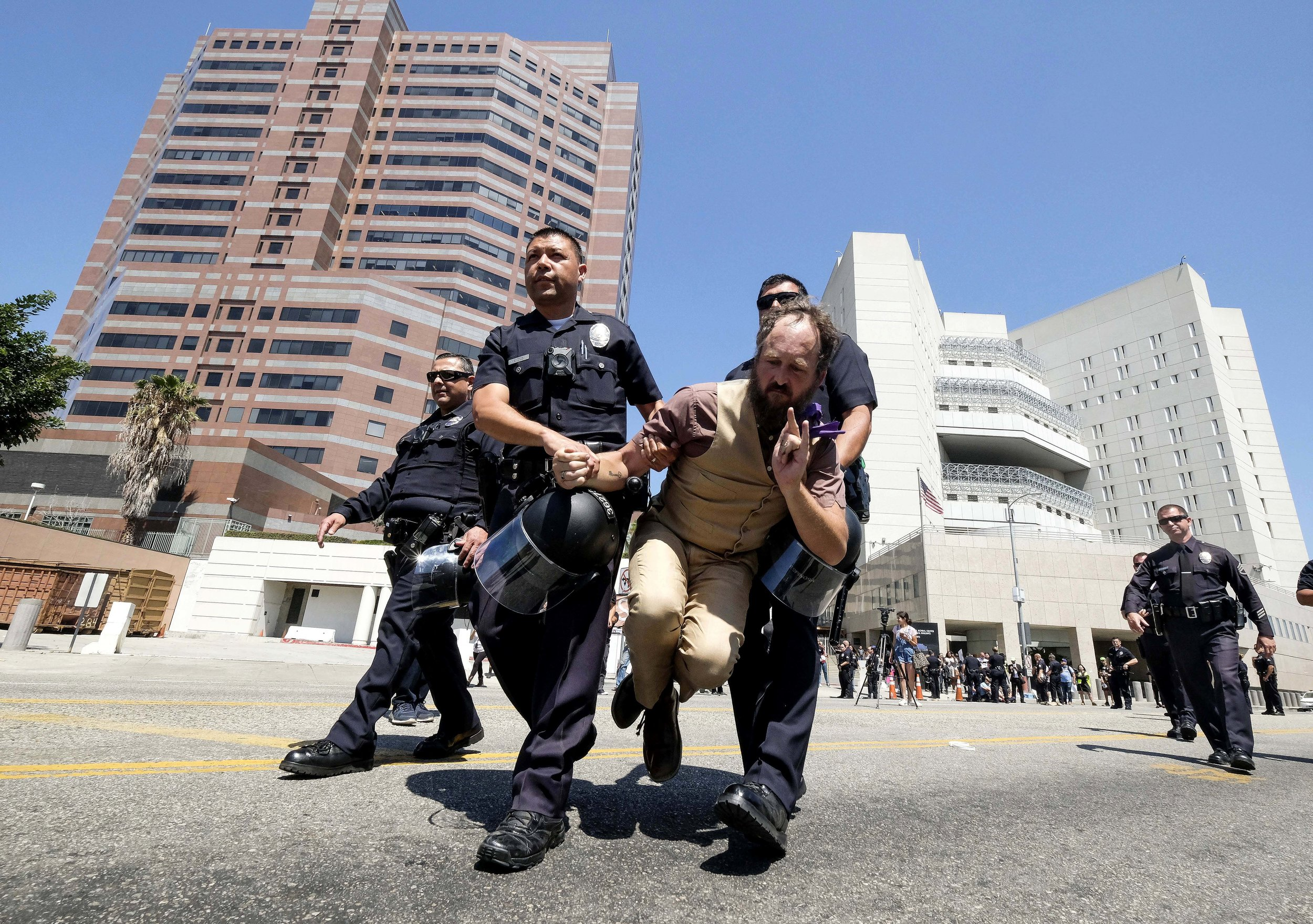 A protester is carried away after being arrested in front of the Immigration and Customs Enforcement facility in downtown Los Angeles on Monday, July 2, 2018. A group of protesters sat down in the street and blocking the entrance to the Immigration and Customs Enforcement headquarters as part of a nationwide call to end Immigration and Customs Enforcement's separation of families.