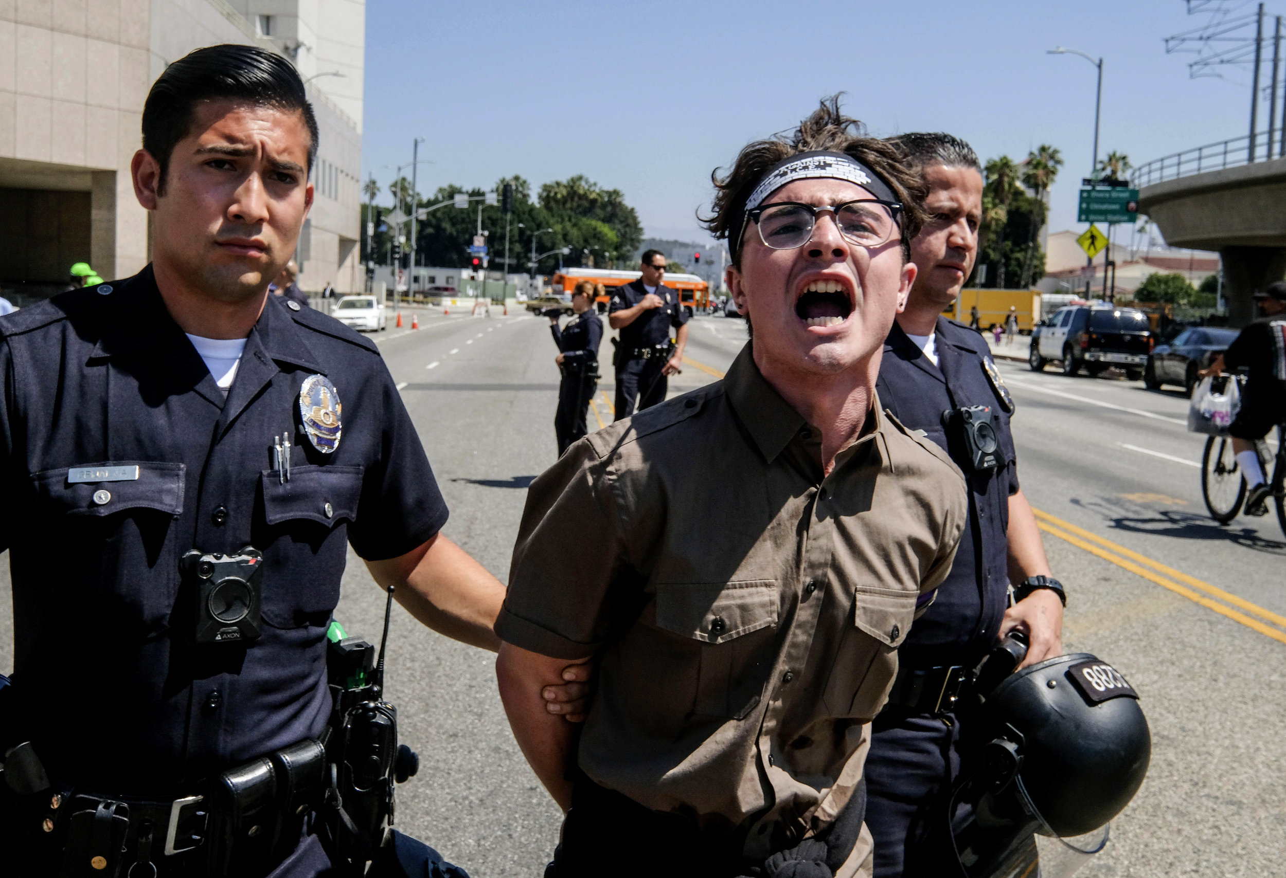 A protester is taken away in cuffs after being arrested in front of the Immigration and Customs Enforcement facility in downtown Los Angeles on Monday, July 2, 2018. A group of protesters sat down in the street and blocking the entrance to the Immigration and Customs Enforcement headquarters as part of a nationwide call to end Immigration and Customs Enforcement's separation of families.
