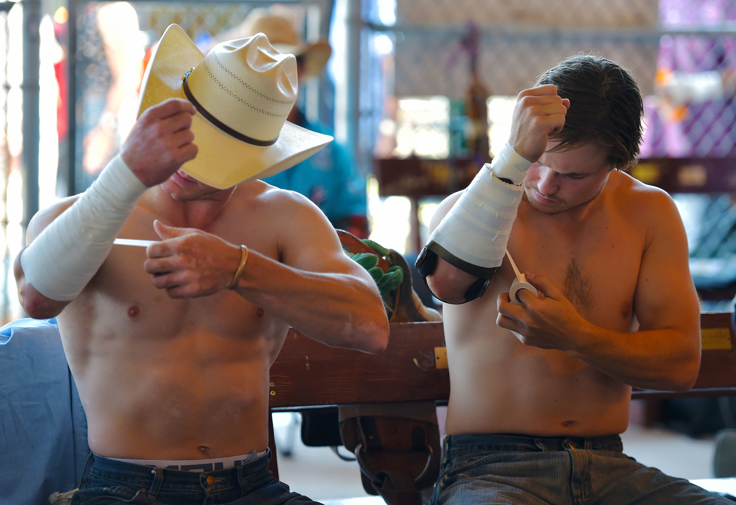 A pair of competitors tape up their arms prior to the 6th performance at the 122nd Cheyenne Frontier Days Rodeo at Frontier Park in Cheyenne, Wyoming Wednesday, July 25, 2018.