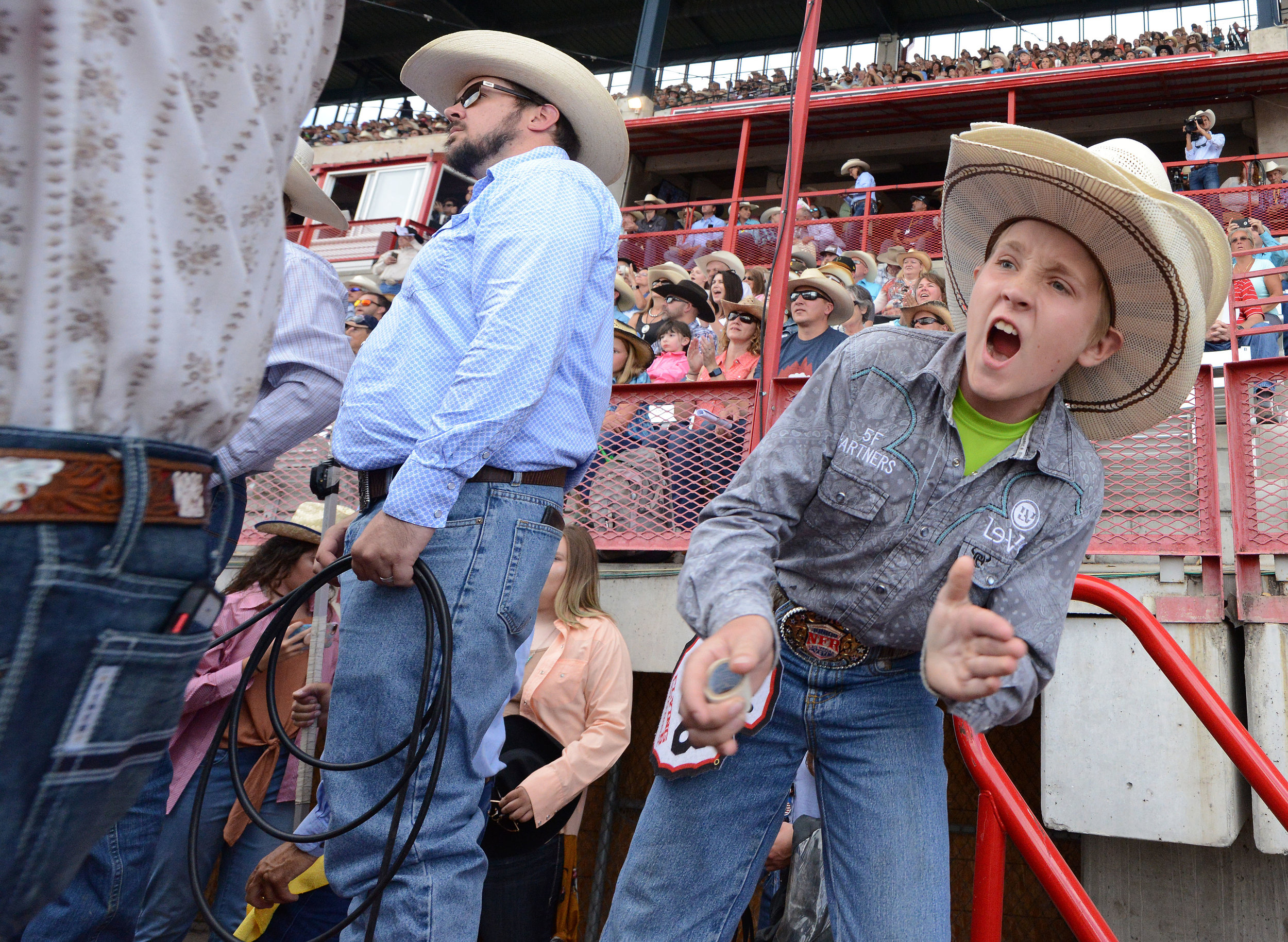 A young mini bull rider cheers on a contestant during the 6th performance at the 122nd Cheyenne Frontier Days Rodeo at Frontier Park in Cheyenne, Wyoming Wednesday, July 25, 2018.