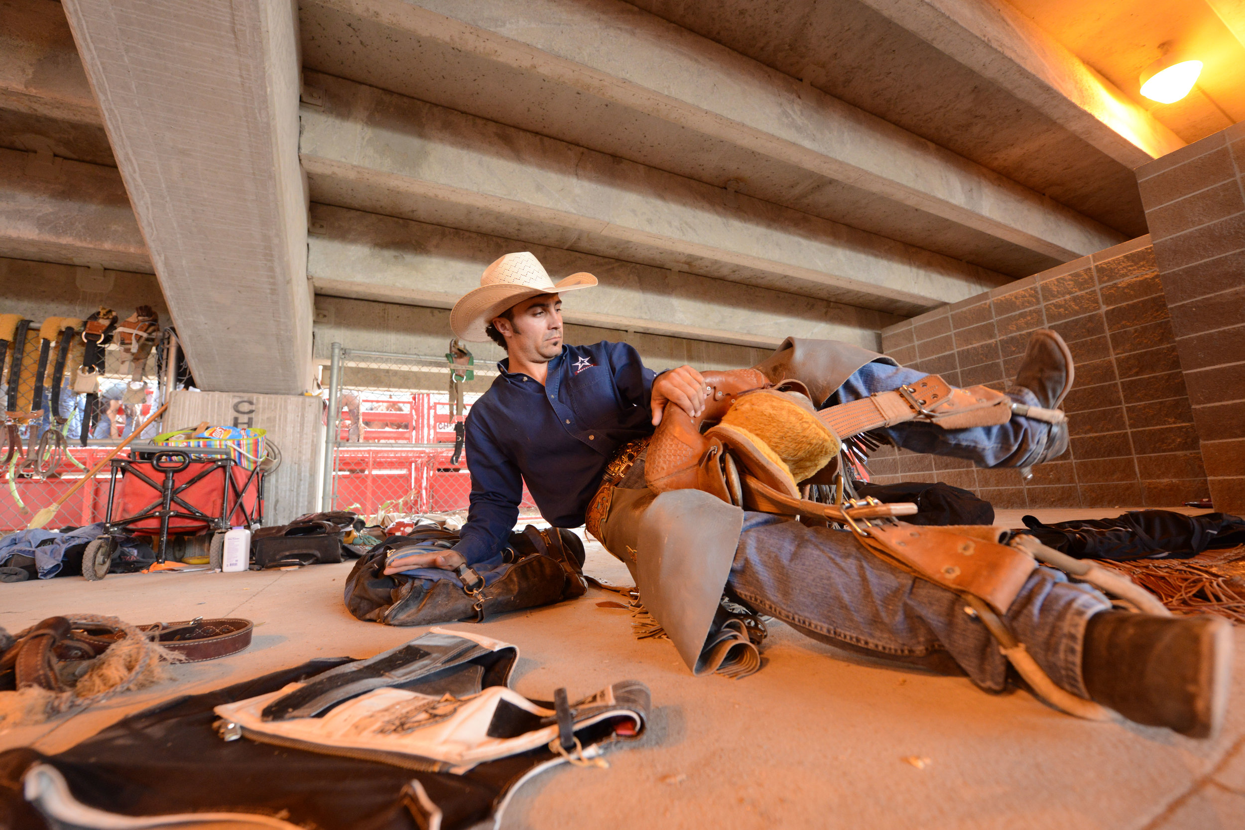 Saddle bronc rider Mitch Pollack, from Twin Falls, Idaho, prepares for his event behind the bucking chutes during the 6th performance at the 122nd Cheyenne Frontier Days Rodeo at Frontier Park in Cheyenne, Wyoming Wednesday, July 25, 2018.
