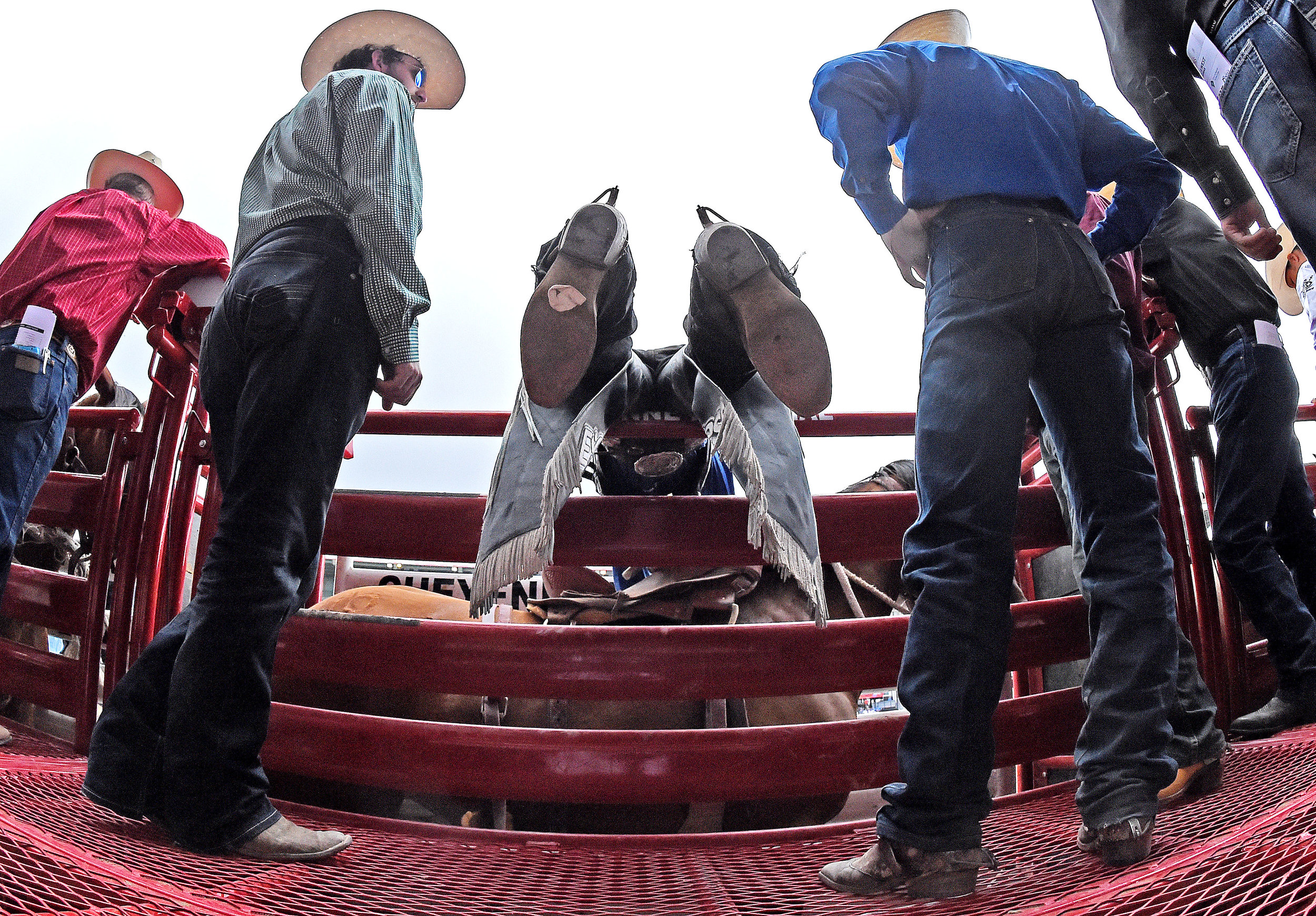 Defending saddle bronc world champion Ryder Wright from Midford, Utah, leans over the bucking chutes as he prepares to ride Chill Wills during the 6th performance at the 122nd Cheyenne Frontier Days Rodeo at Frontier Park in Cheyenne, Wyoming Wednesday, July 25, 2018.