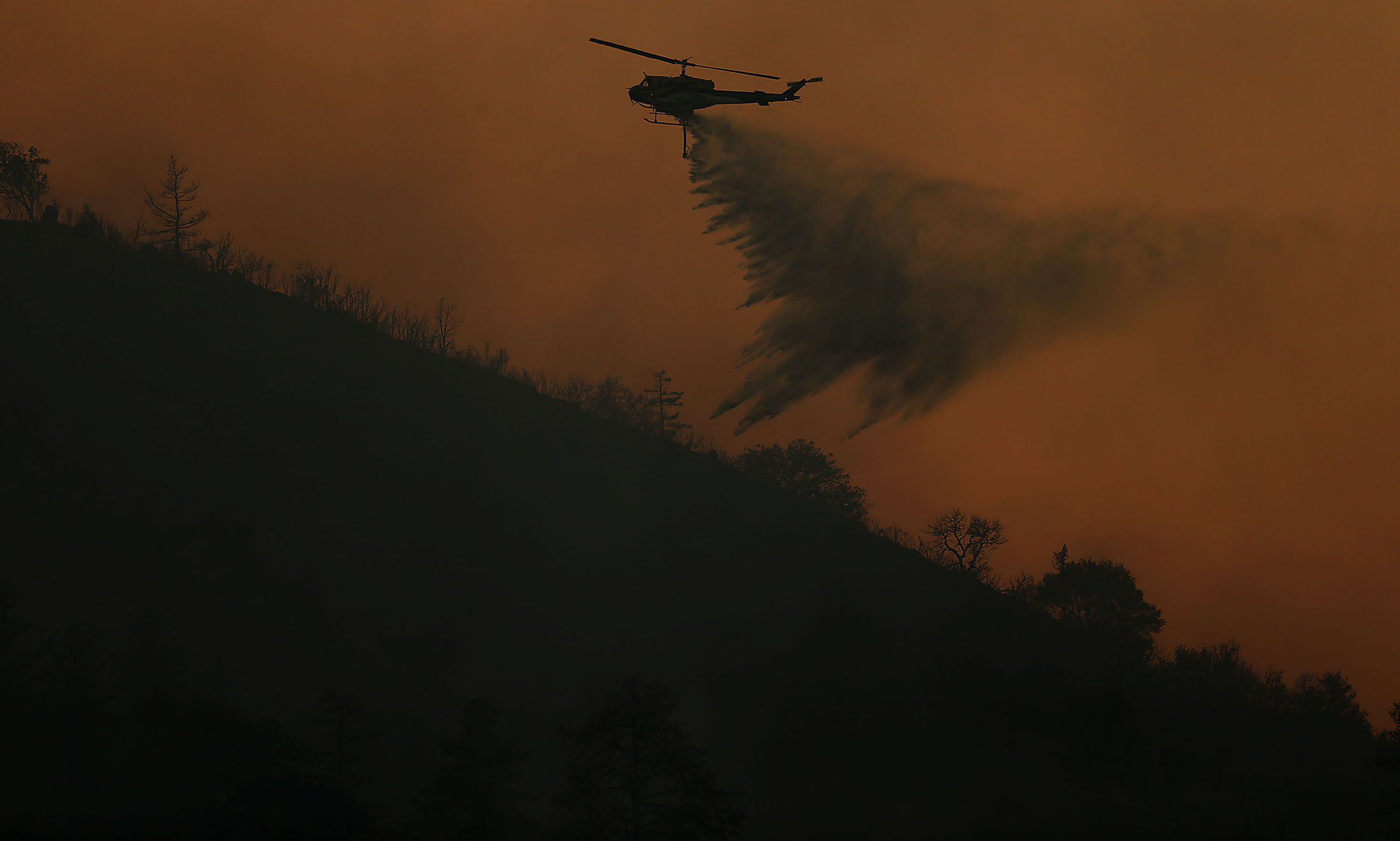 A water dropping helicopter makes a drop on the Cranston fire above Camp Keene Road along HWY 74 north of Lake Hemet in the San Bernardino National Forest in Mountain Center on Thursday, July 26, 2018.