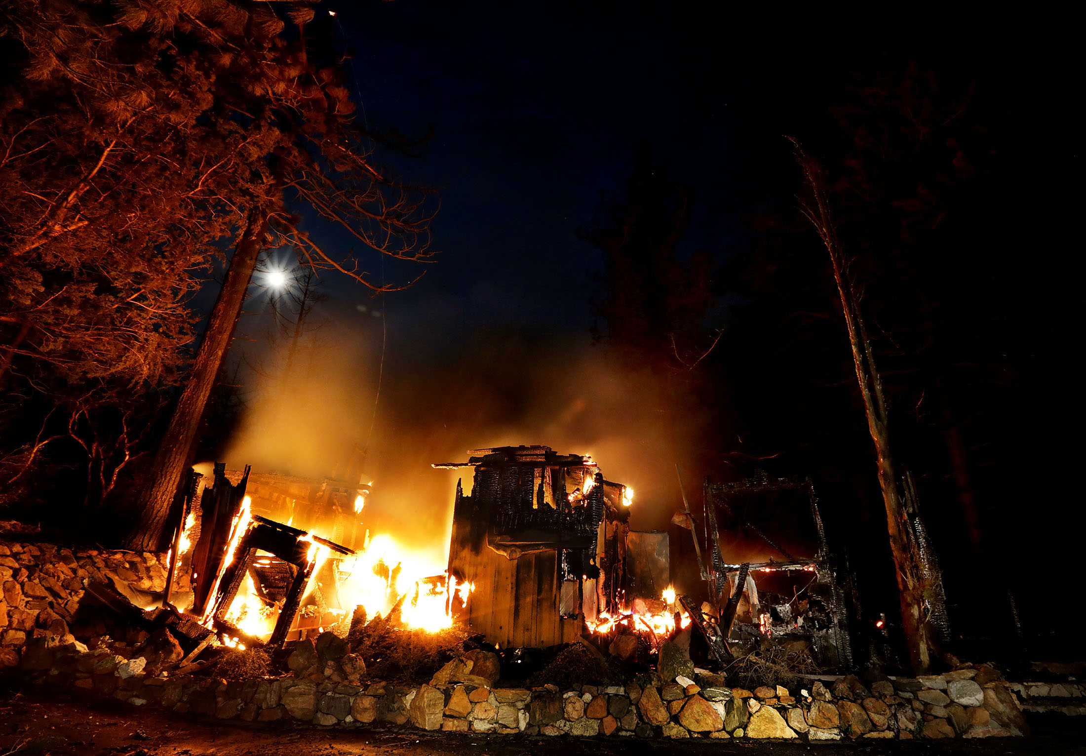 A home on Deer Foot Lane burns into the night on Deer Foot Lane as the Cranston fire slows in the cool night air after during more than 3,500 acres in the San Bernardino National Forest in Idyllwild on Wednesday, July 25, 2018.