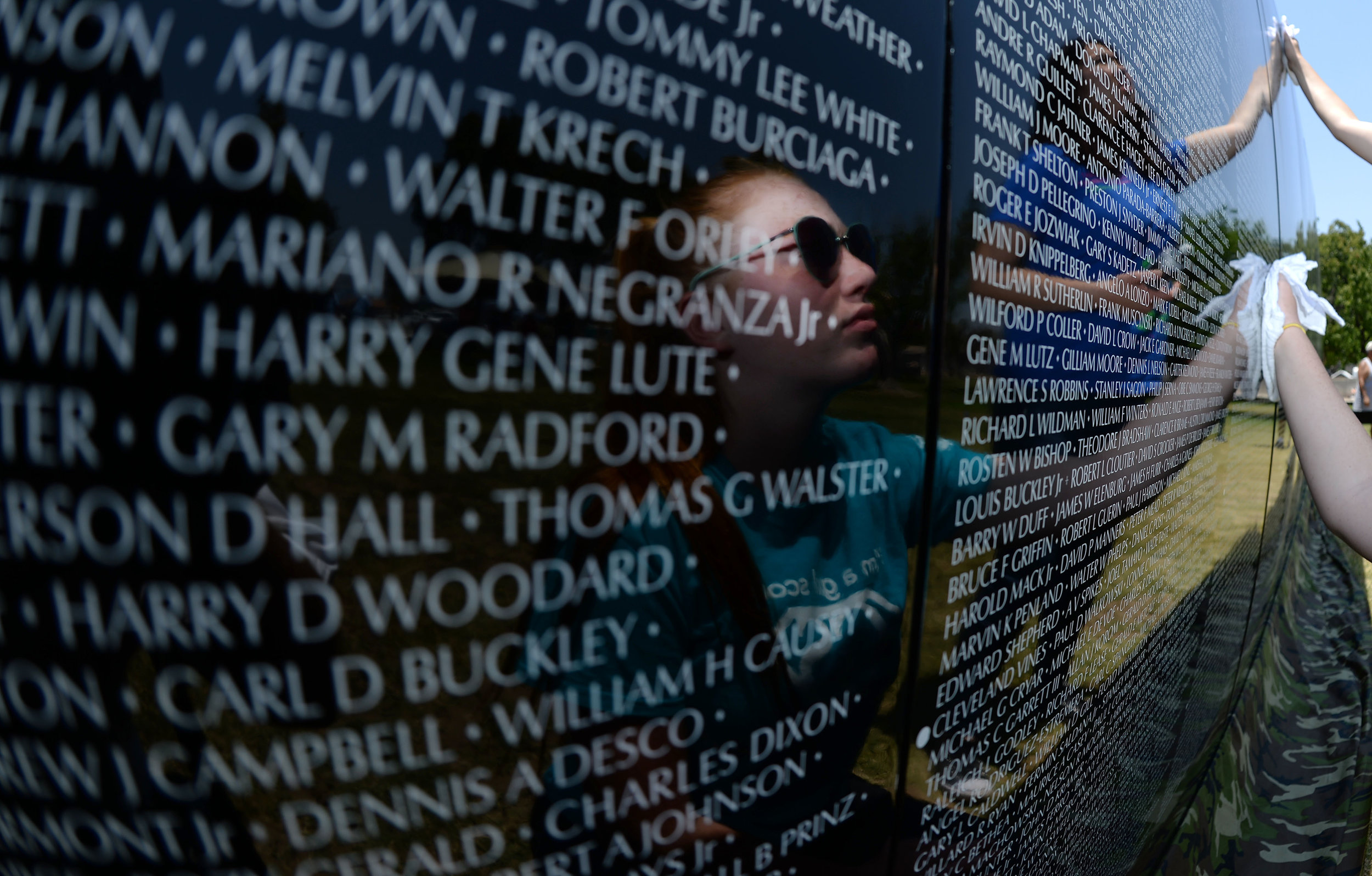 Skylar Littlefield, 16 from Grand Terrace, cleans the face of one of the 70 panels being installed of the Vietnam Moving Wall Thursday at Ayala Park in Bloomington. Volunteers, many being Vietnam veterans, helped construct the Vietnam Moving Wall in Ayala Park in Bloomington Thursday June 7, 2018. The wall, containing 58,318 names, with 132 being from San Bernardino County, will be on display 24-hours a day beginning Friday and lasting through Monday.