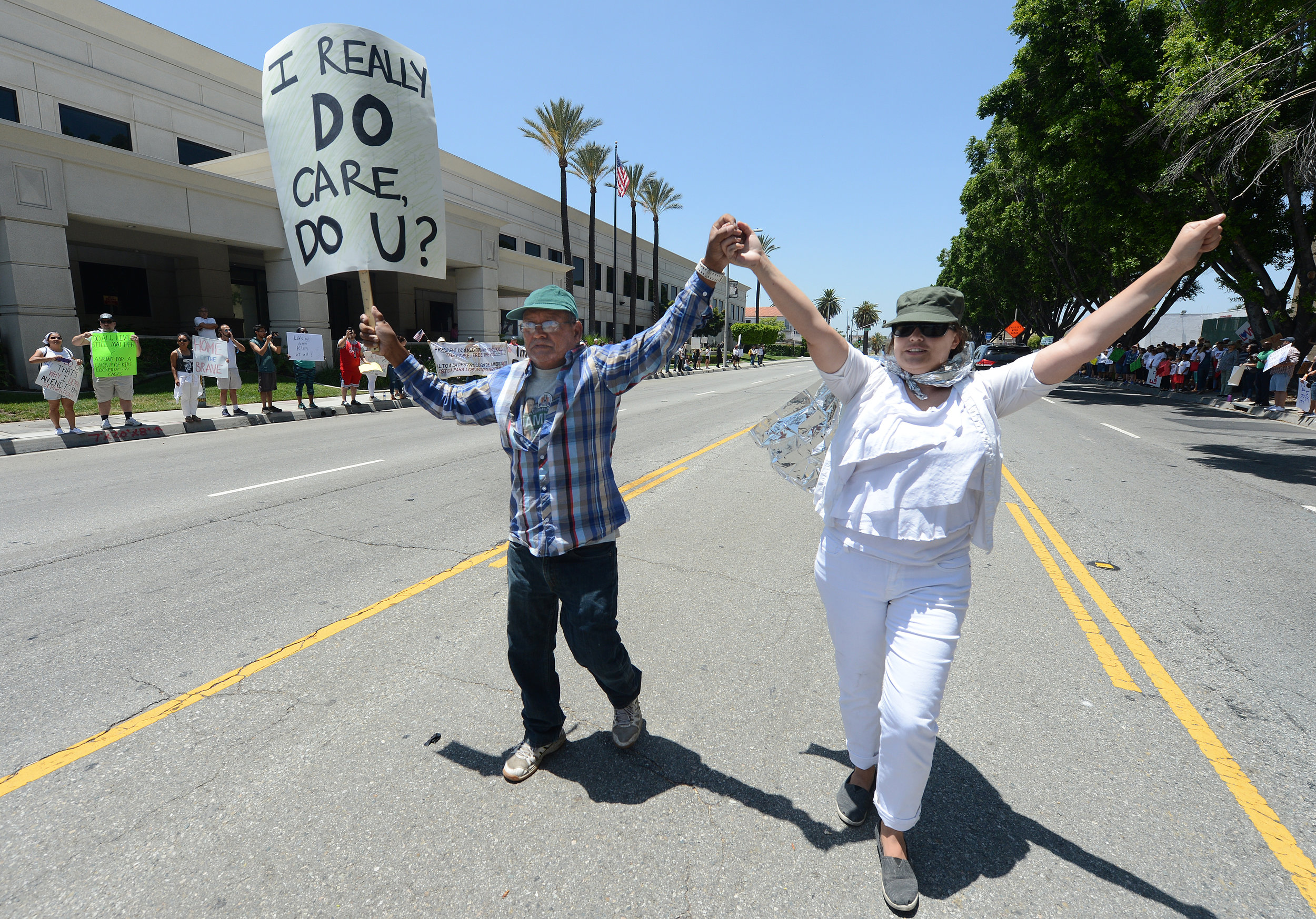 Subhash Arora (left), from San Bernardino, and Emilie Brill (right), from Loma Linda, protest in the middle of W. Rialto Avenue as approximately 450 others protesters look on as a part of the Families Belong Together rally outside the office of Homeland Security in San Bernardino on Saturday, June 30, 2018. The peaceful group gathered in support of immigrant families that have been separated by federal agents under U.S. policy.