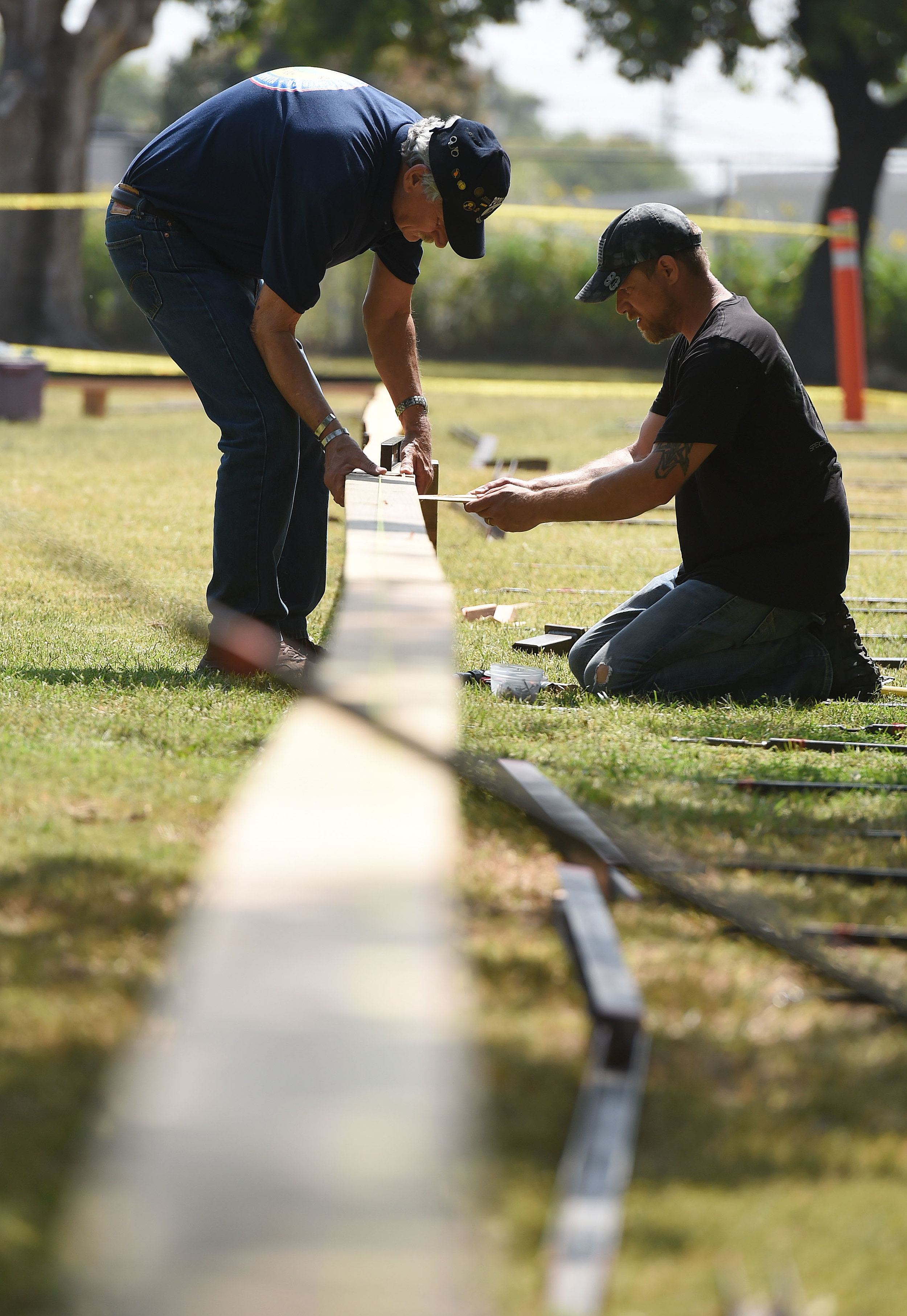 Vietnam Army veteran Steve Mackey (left), 68 from Jurupa Valley, assists Aaron Gray (right), 41 from White Pine, Michigan, as they install the base for the Vietnam Moving Wall Thursday at Ayala Park in Bloomington. Volunteers, many being Vietnam veterans, helped construct the Vietnam Moving Wall in Ayala Park in Bloomington Thursday June 7, 2018. The wall, containing 58,318 names, with 132 being from San Bernardino County, will be on display 24-hours a day beginning Friday and lasting through Monday.