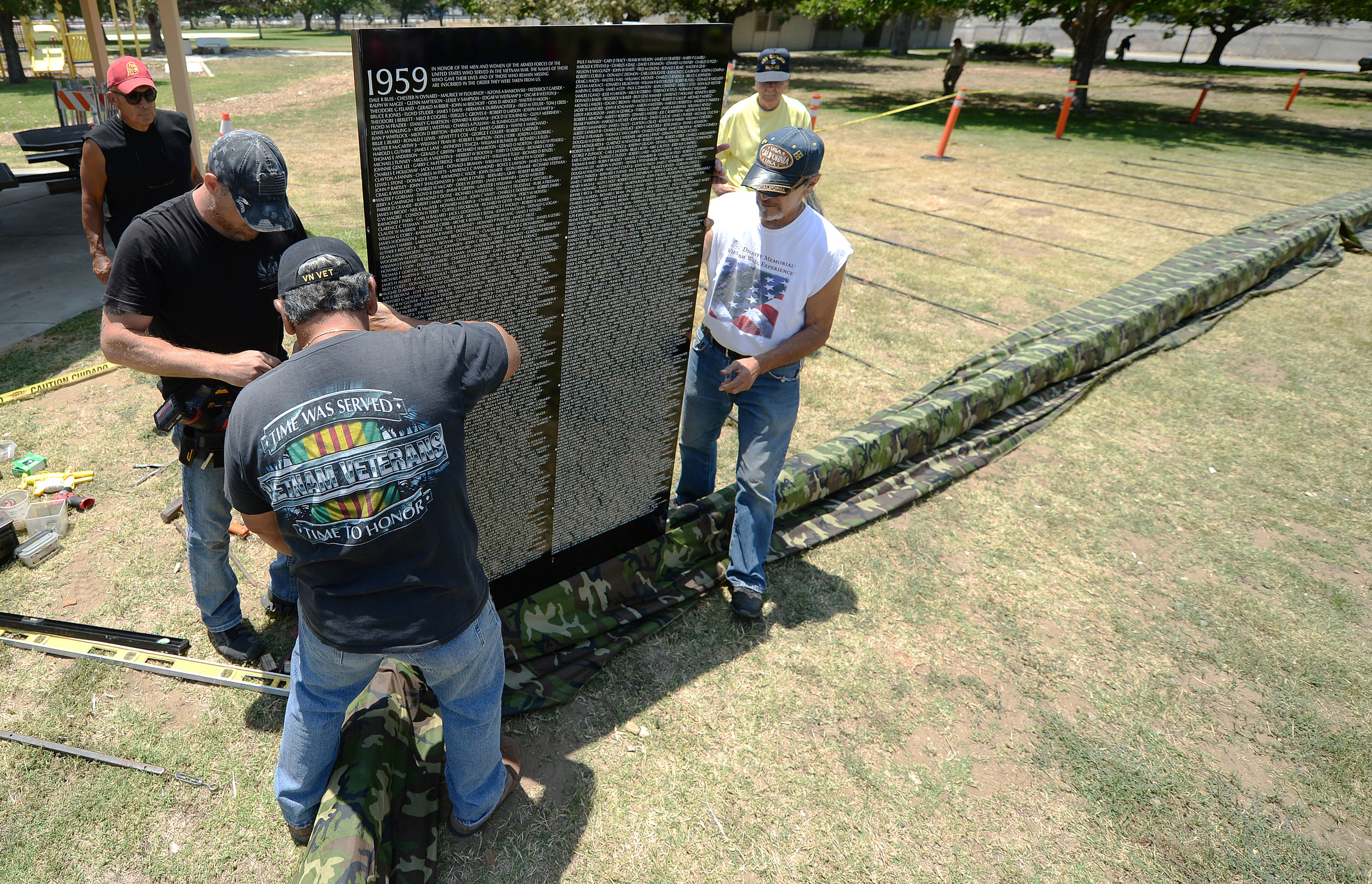 Volunteers install the first of 70 panels of the Vietnam Moving Wall Thursday at Ayala Park in Bloomington. Volunteers, many being Vietnam veterans, helped construct the Vietnam Moving Wall in Ayala Park in Bloomington Thursday June 7, 2018. The wall, containing 58,318 names, with 132 being from San Bernardino County, will be on display 24-hours a day beginning Friday and lasting through Monday.