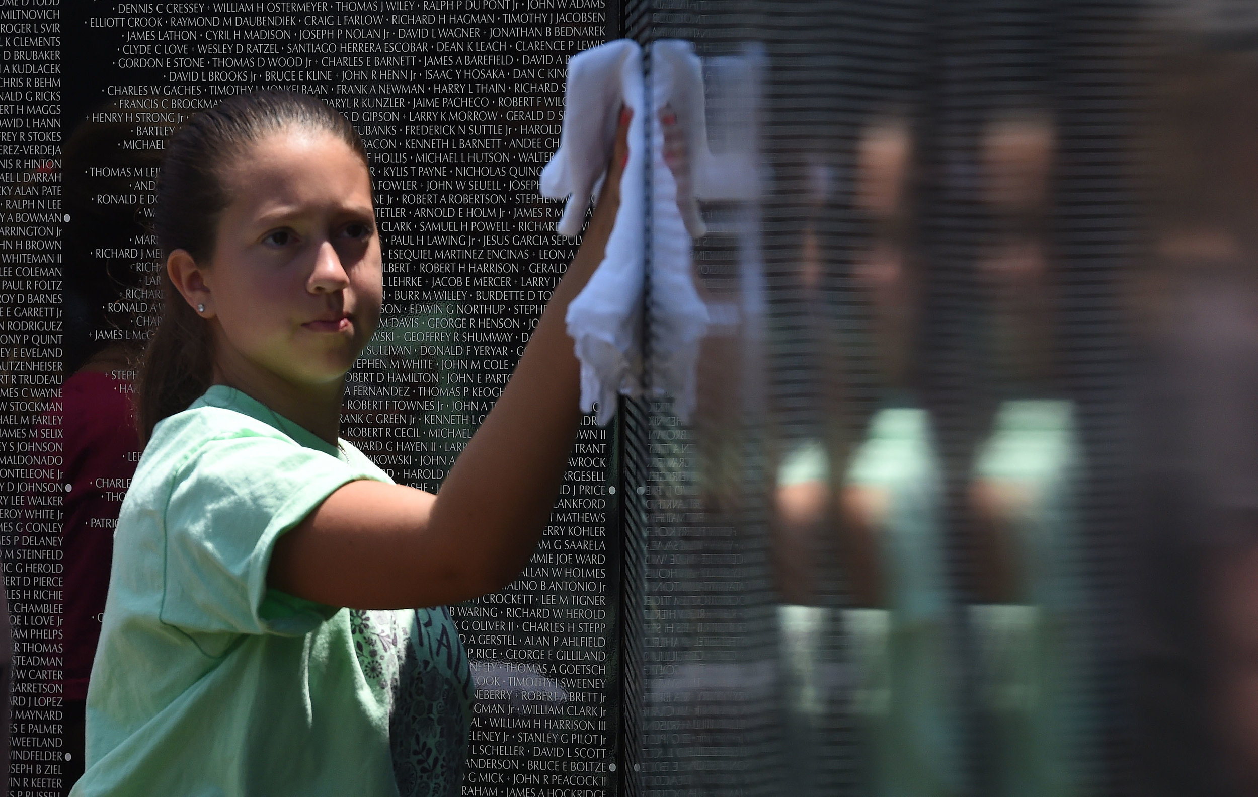 Alaina Gaitan, 12 from Grand Terrace, helps clean a panel of the Vietnam Moving Wall as it is being installed Thursday at Ayala Park in Bloomington. Volunteers, many being Vietnam veterans, helped construct the Vietnam Moving Wall in Ayala Park in Bloomington Thursday June 7, 2018. The wall, containing 58,318 names, with 132 being from San Bernardino County, will be on display 24-hours a day beginning Friday and lasting through Monday.
