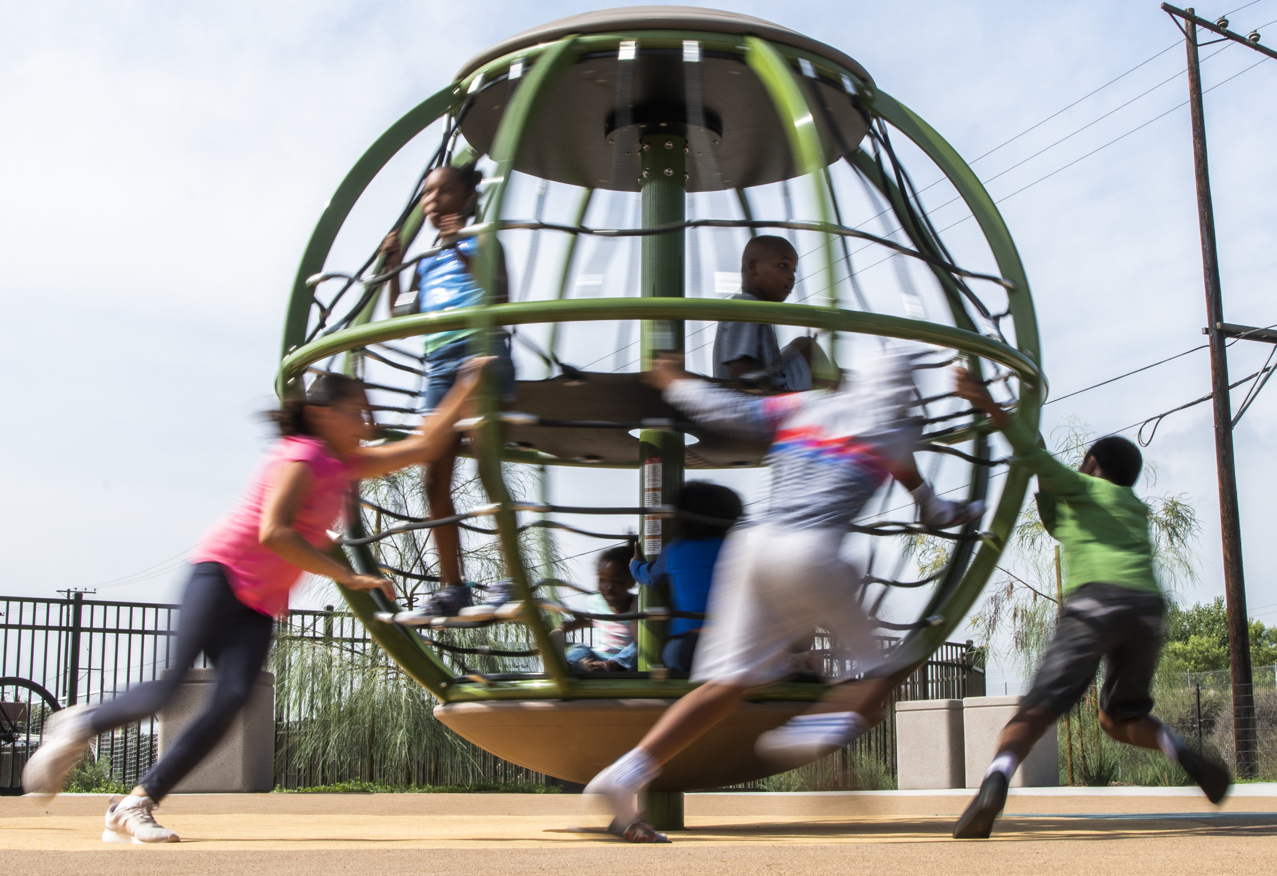 Kids spin a glob like a merry-go-round during the grand opening of David Molina Park in Long Beach August 28, 2018.