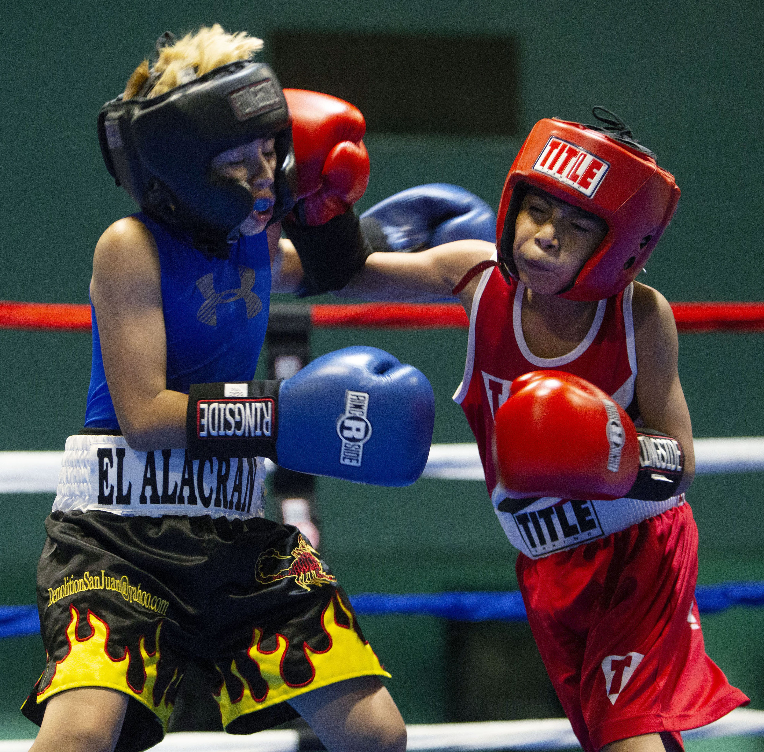 FTP Boxing's Adrian Herrera, 9, lands a punch to the face of Compton Boxing's Alan Brizuela, 8, in their bout during the Future Olympics Champions at  Lake Perris Sports Pavilion in Perris on Saturday, August 18, 2018.