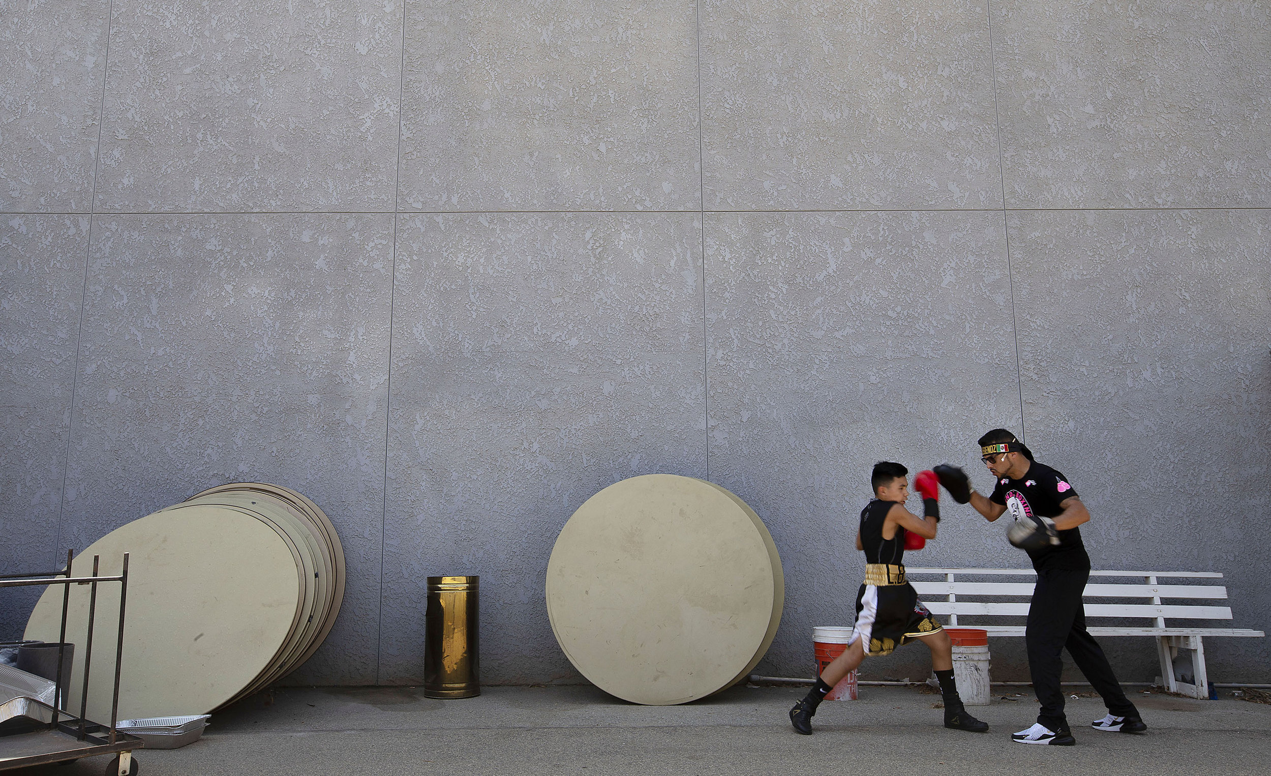 Legendz Boxing Club's Jonathan Trevino, 12, warms up outside with trainer Jose Ruvalcaba for the first bout of the day during the Future Olympics Champions at  Lake Perris Sports Pavilion in Perris on Saturday, August 18, 2018.