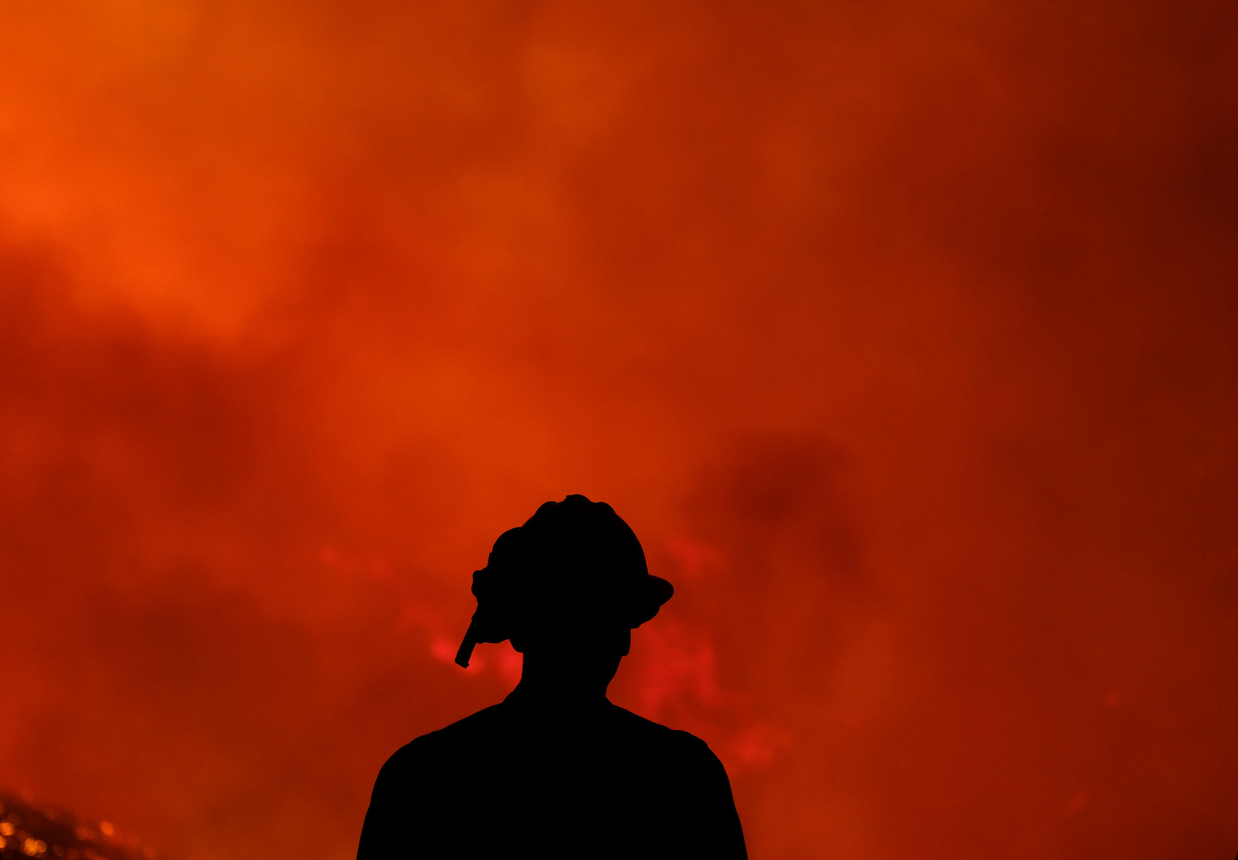 A firefighters keep watch the Holy Fire burning in the Cleveland National Forest in Lake Elsinore, Calif., Thursday, Aug. 9, 2018.