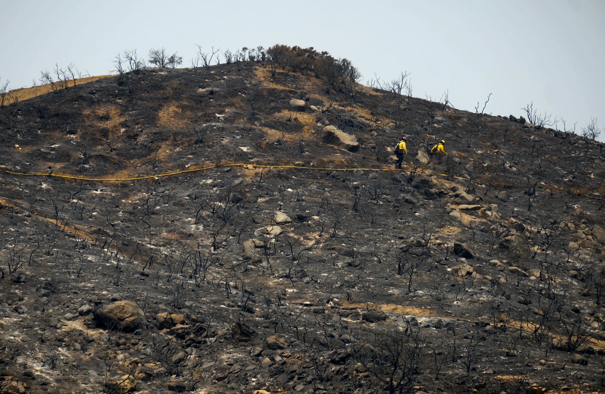 Firefighters walk through the burned area at the Holy Fire in Lake Elsinore, California, southeast of Los Angeles, on August 11, 2018. The fire has burned 21,473 acres and was 29 percent contained as of 8:30 a.m. Saturday, according to the Cleveland National Forest.