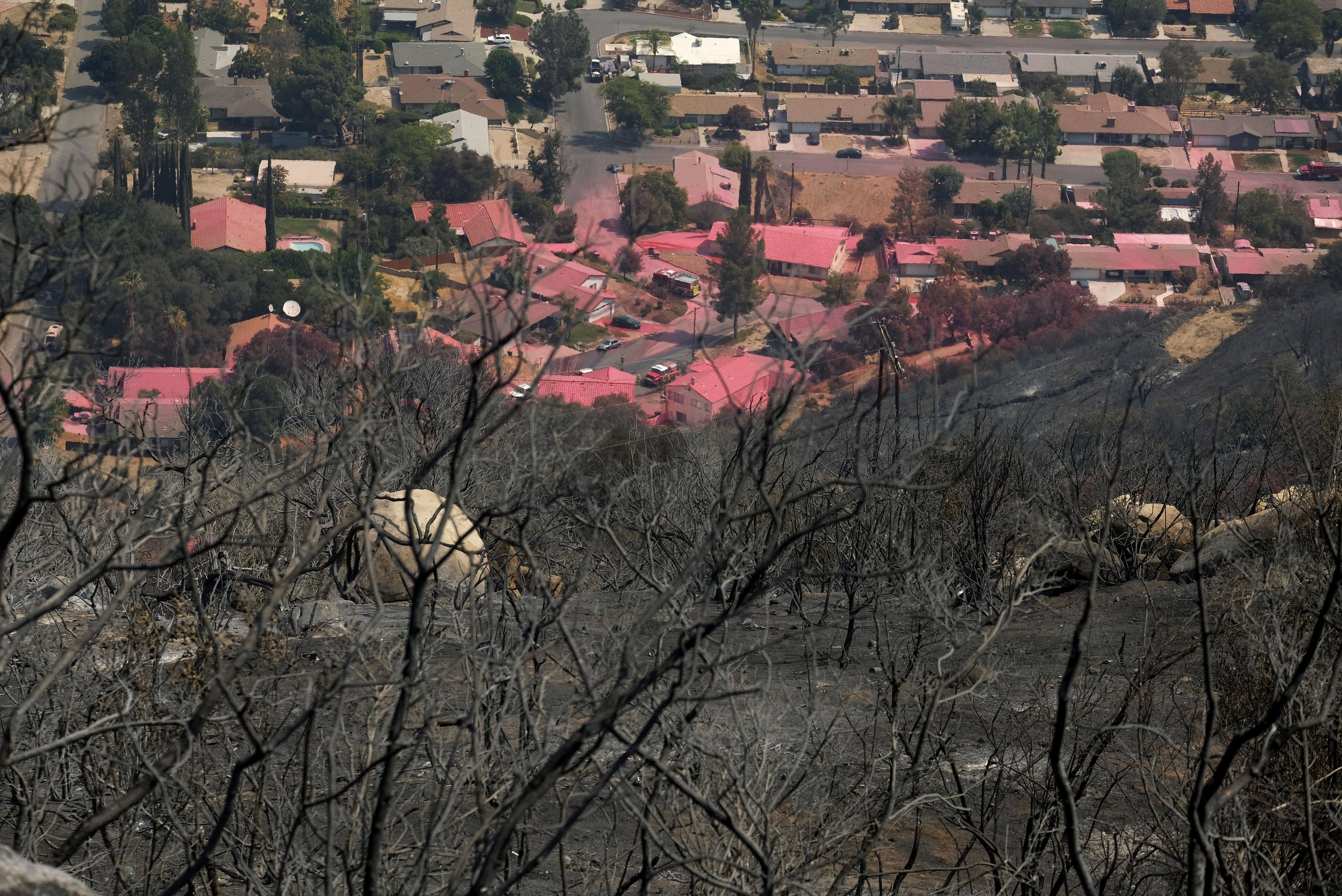 Homes are covered in pink fire retardant at the Holy Fire in Lake Elsinore, California, southeast of Los Angeles, on August 11, 2018. The fire has burned 21,473 acres and was 29 percent contained as of 8:30 a.m. Saturday, according to the Cleveland National Forest.