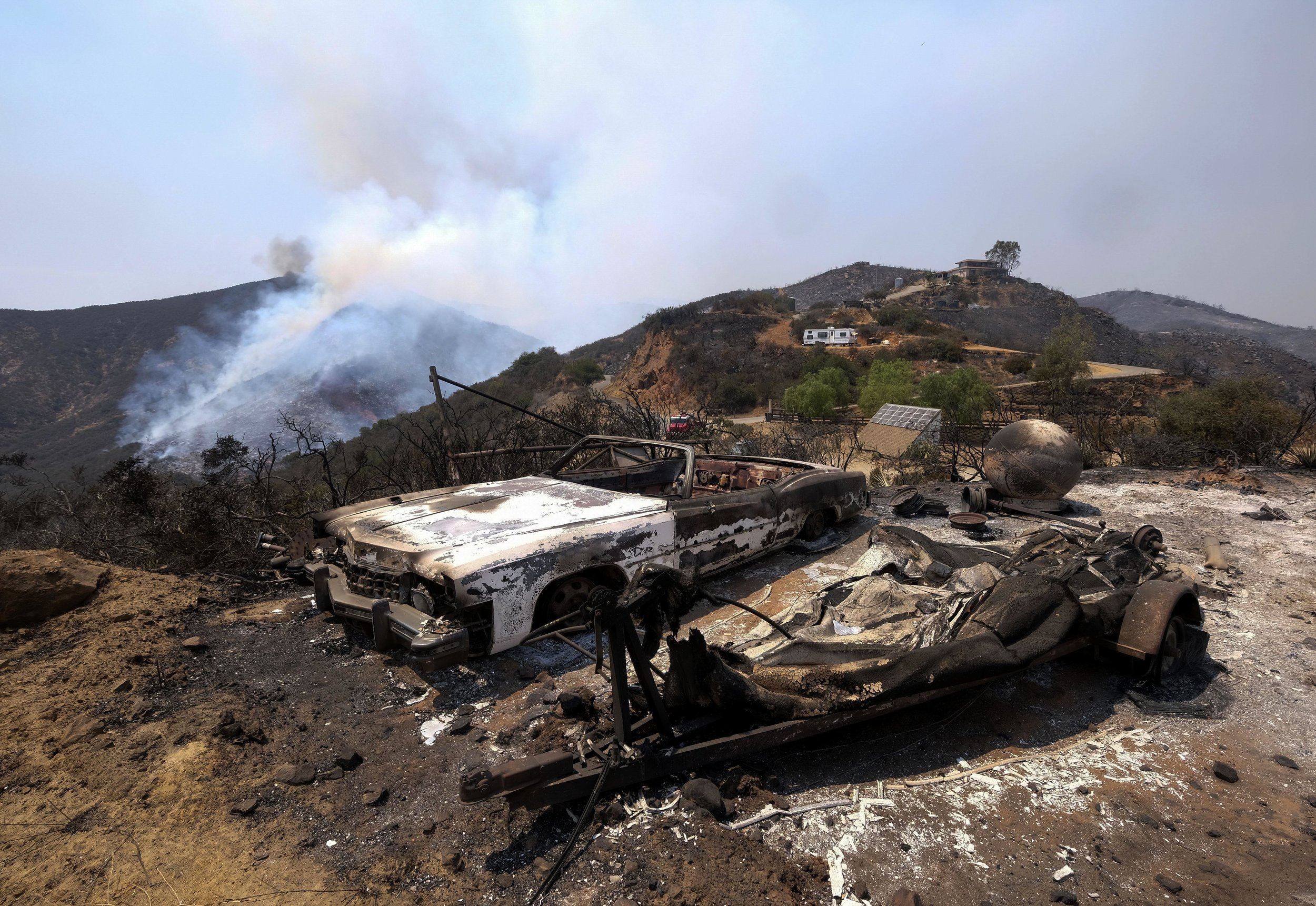 The charred remains of burned-out cars are seen at the Holy Fire in Lake Elsinore, California, southeast of Los Angeles, on August 11, 2018. The fire has burned 21,473 acres and was 29 percent contained as of 8:30 a.m. Saturday, according to the Cleveland National Forest.