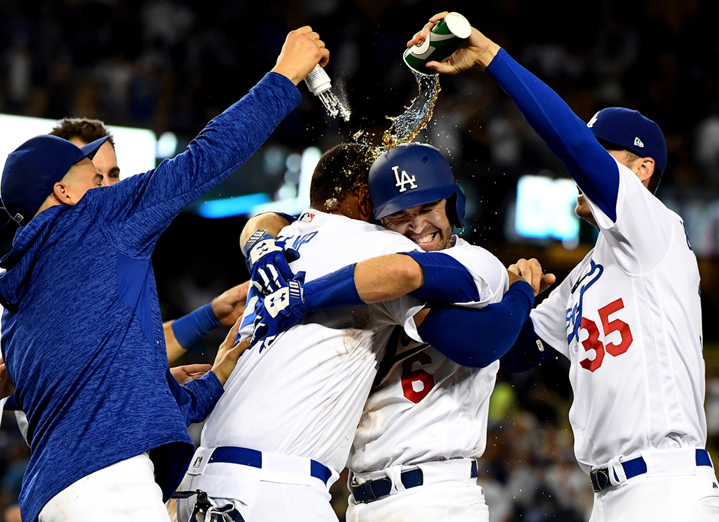 Los Angeles Dodgers' Brian Dozier (6) is mobbed by teammates after hitting the game winning sac fly ball as teammate Yasmani Grandal (not pictured) scored to defeat the San Francisco Giants 4-3 in the twelfth inning of Major League Baseball game at Dodger Stadium on Wednesday, Aug. 15, 2018 in Los Angeles.