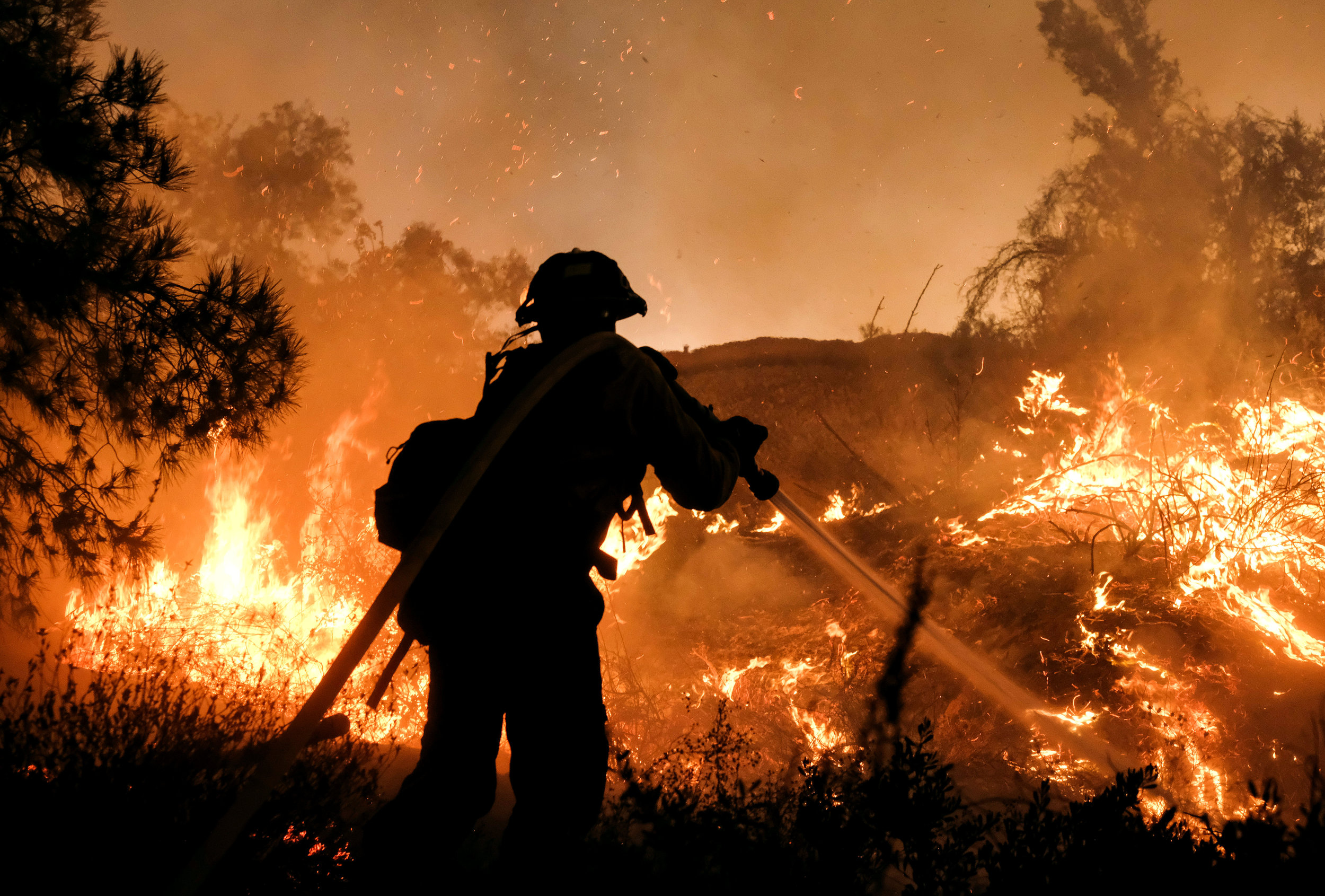 A firefighter battles the Holy Fire burning in the Cleveland National Forest along a hillside at Temescal Valley in Corona, Calif., Thursday, Aug. 9, 2018.
