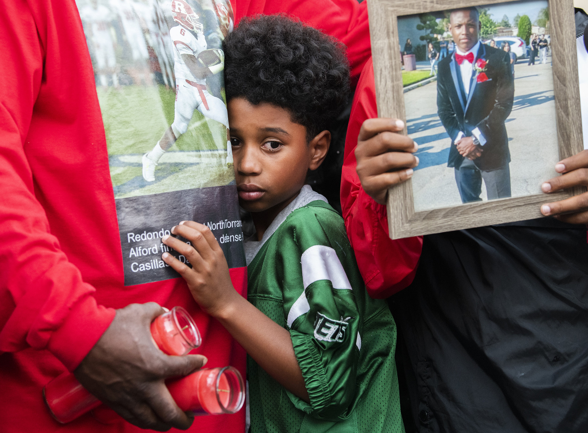 Amari Alford, 10, hugs his father during a vigil for his older brother Guy Alford III, 20, who was shot and killed in a drive-through fast food restaurant the two nights before In Long Beach September 27, 2018.