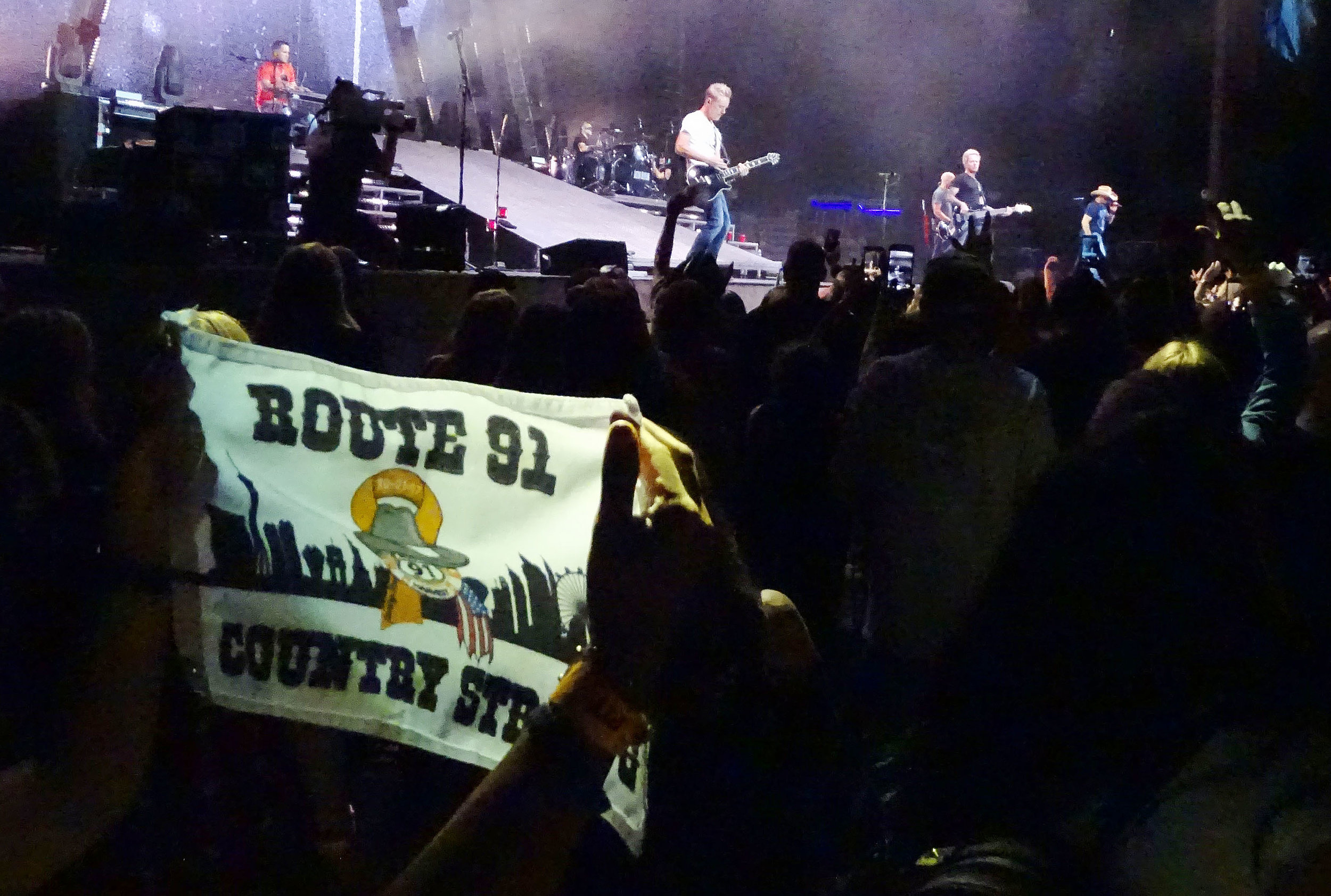 A Route 91 Harvest Festival survivor displays a small banner as Jason Aldean performs Thursday night September 20, 2018 in Chula Vista.