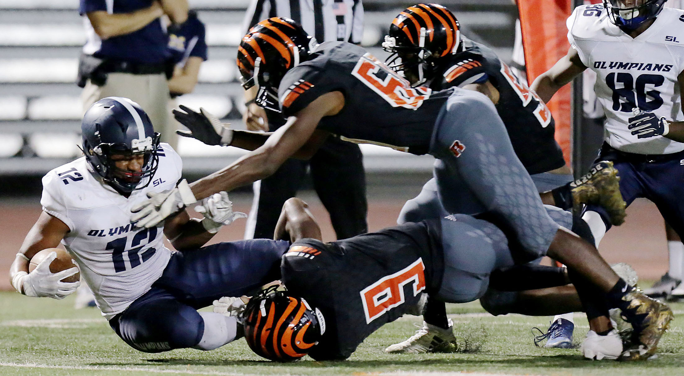 San Diego Mesa's Austin Denson #12 is taken down by Riverside City College defenders after the catch in the second half of the game at Wheelock Field  in Riverside on Saturday, September 29, 2018.