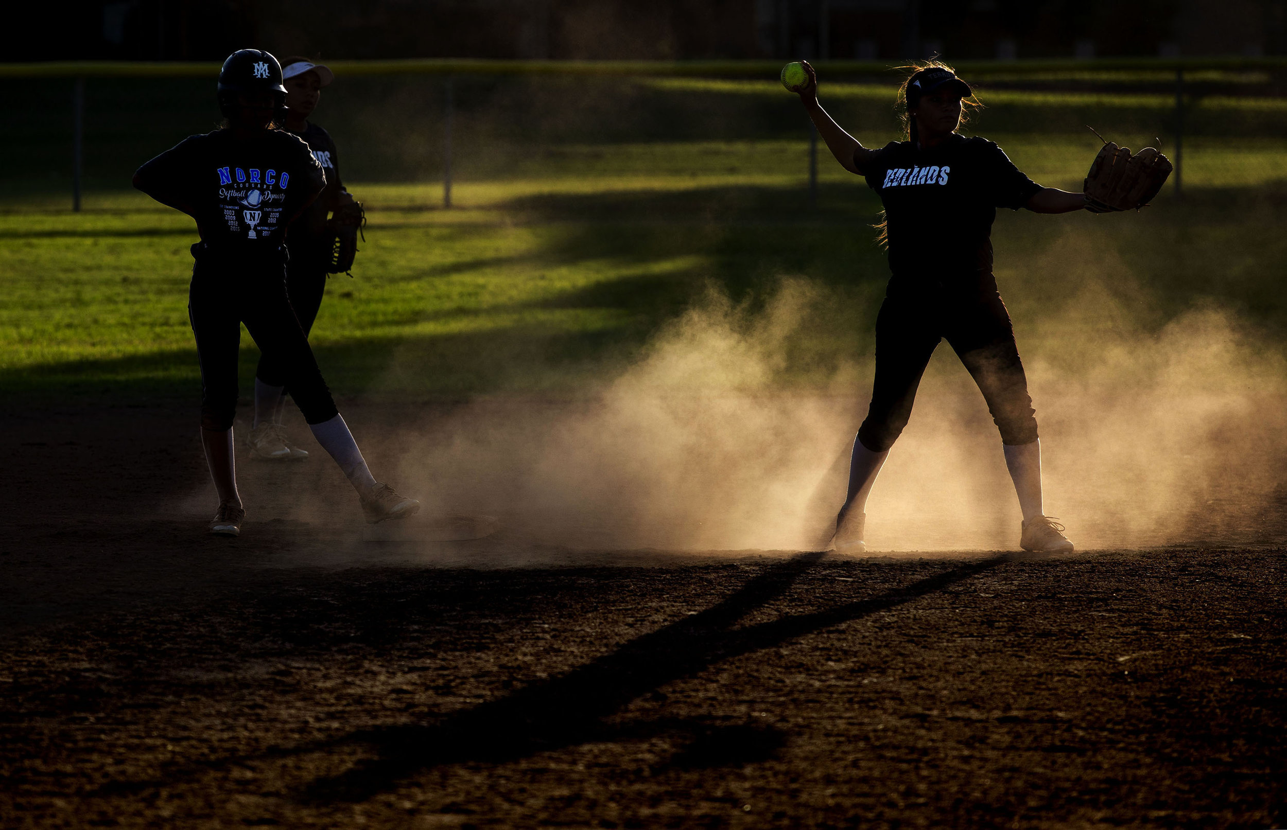 The dust rises after a Norco player steals second base against Redlands during a game La Sierra Park in Riverside on Wednesday, September 26, 2018.