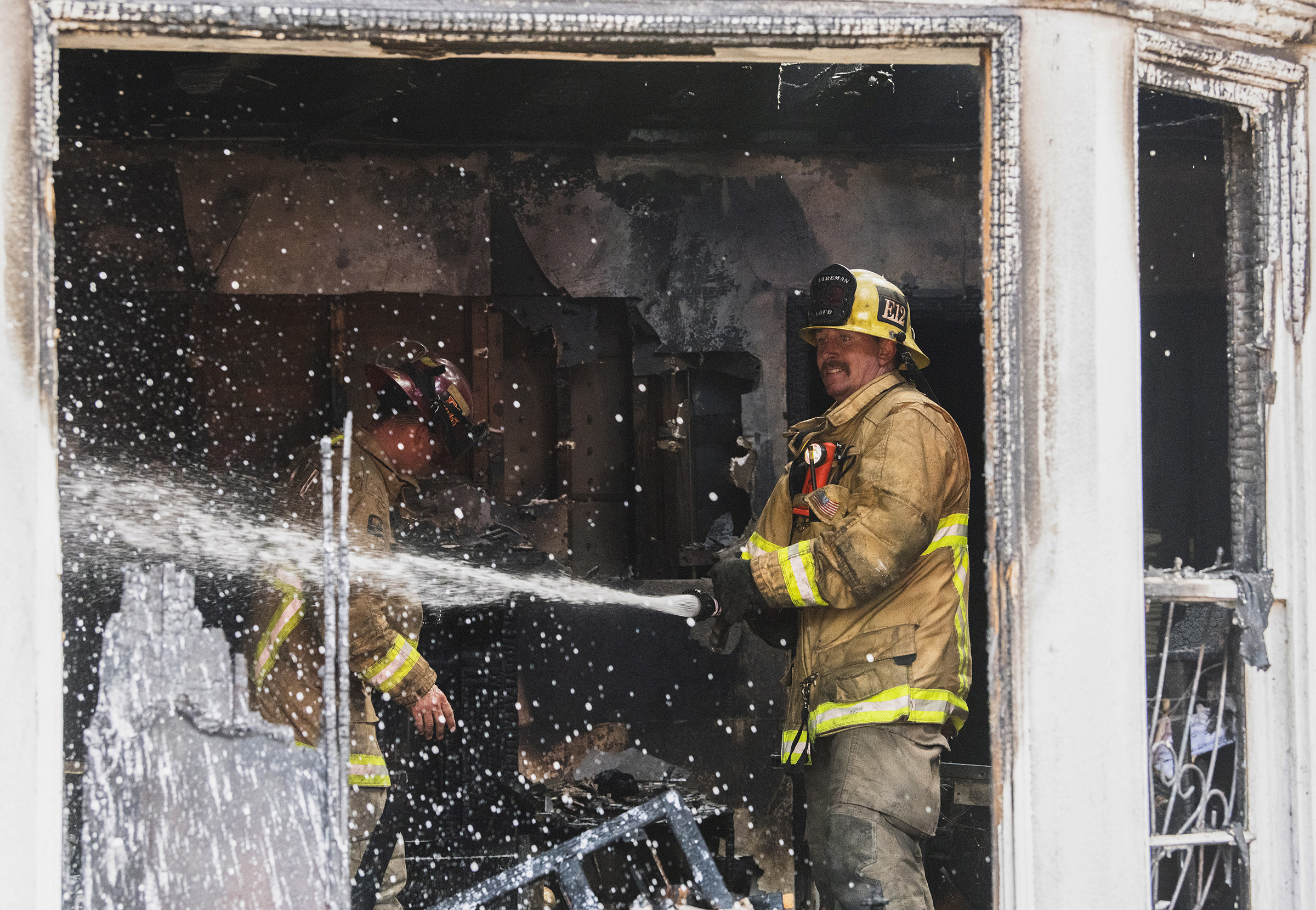 A firefighter puts out hot spots inside the home as Long Beach firefighters knock down an abandoned home fire at Daisy Avenue and Burnett Street in Long Beach September 4, 2018.