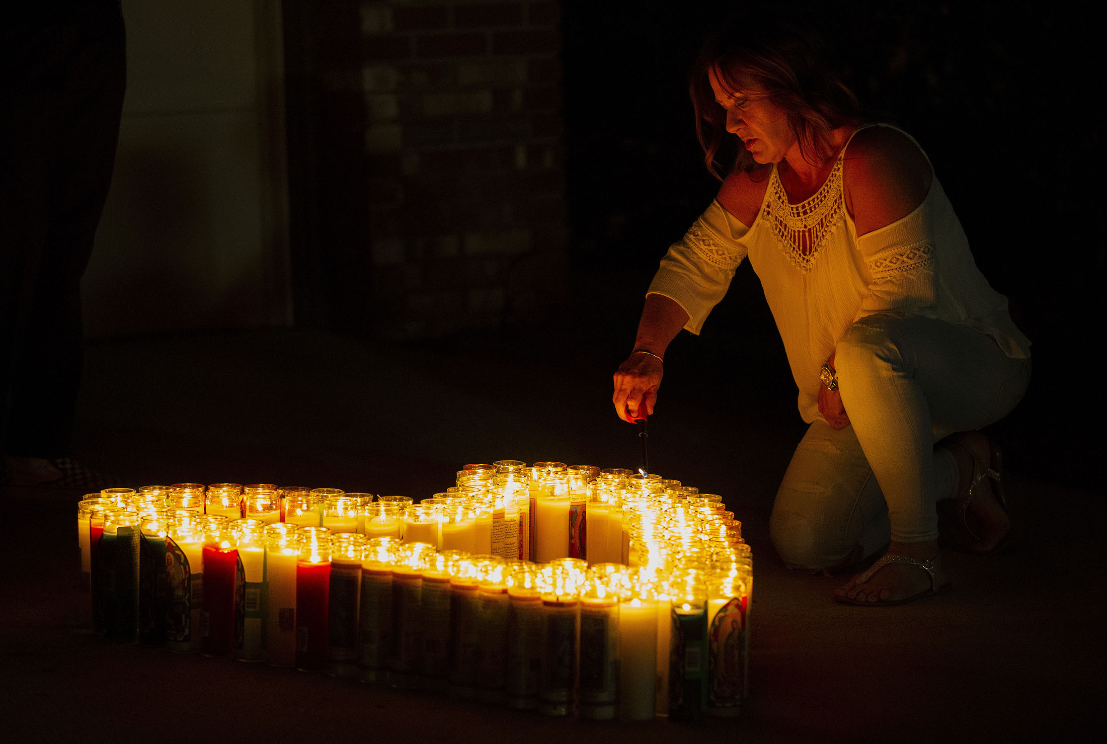 A woman lights candles in the shape of the heart during a candlelight vigil for Leslie Pray, 54, who was killed Saturday while riding her bike along Mills Avenue near Radcliffe Drive in Claremont on Monday, November 5, 2018.