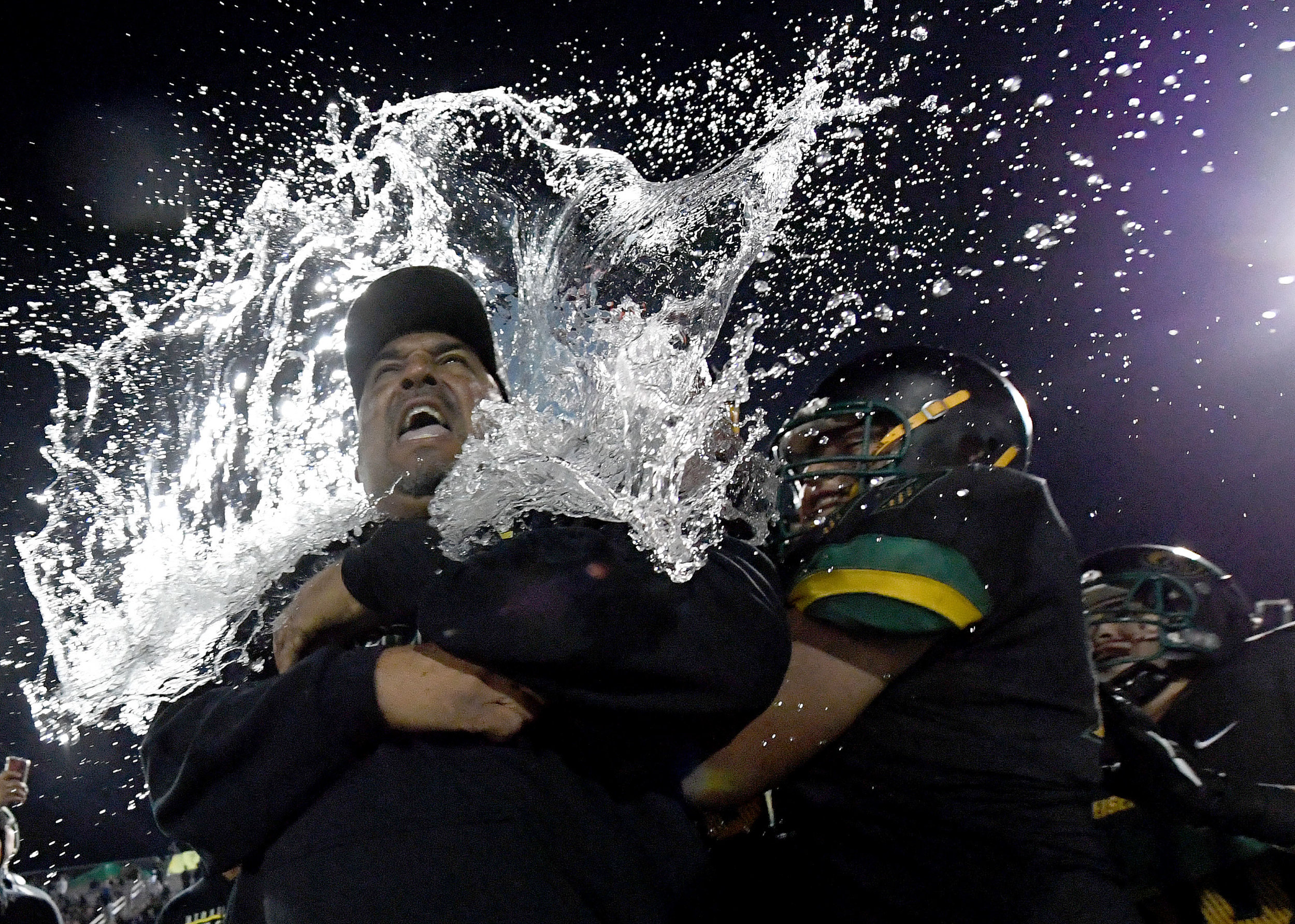 Eisenhower head coach Al Brown gets drenched with water by his players after defeating Highland 35-18 in Rialto, Saturday night November 24, 2018 after winning the CIF Division 10 prep football championship.