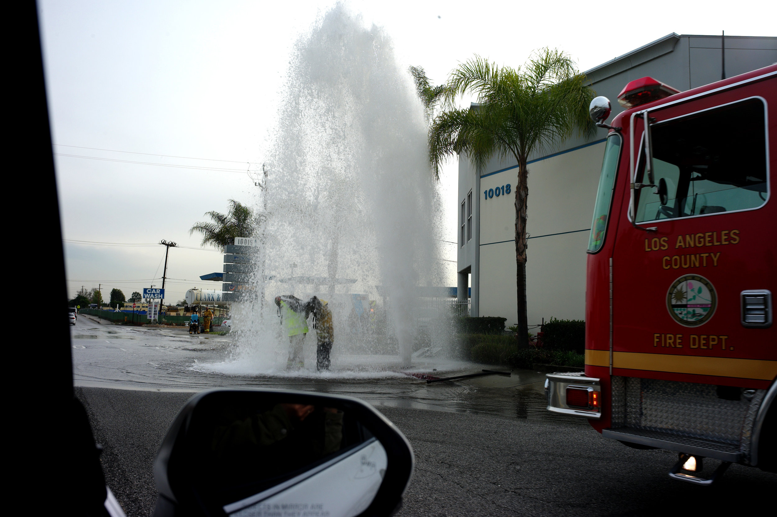 Firefighters try to turn off a broken water main on Lower Azusa road in El Monte on Dec. 21, 2018.