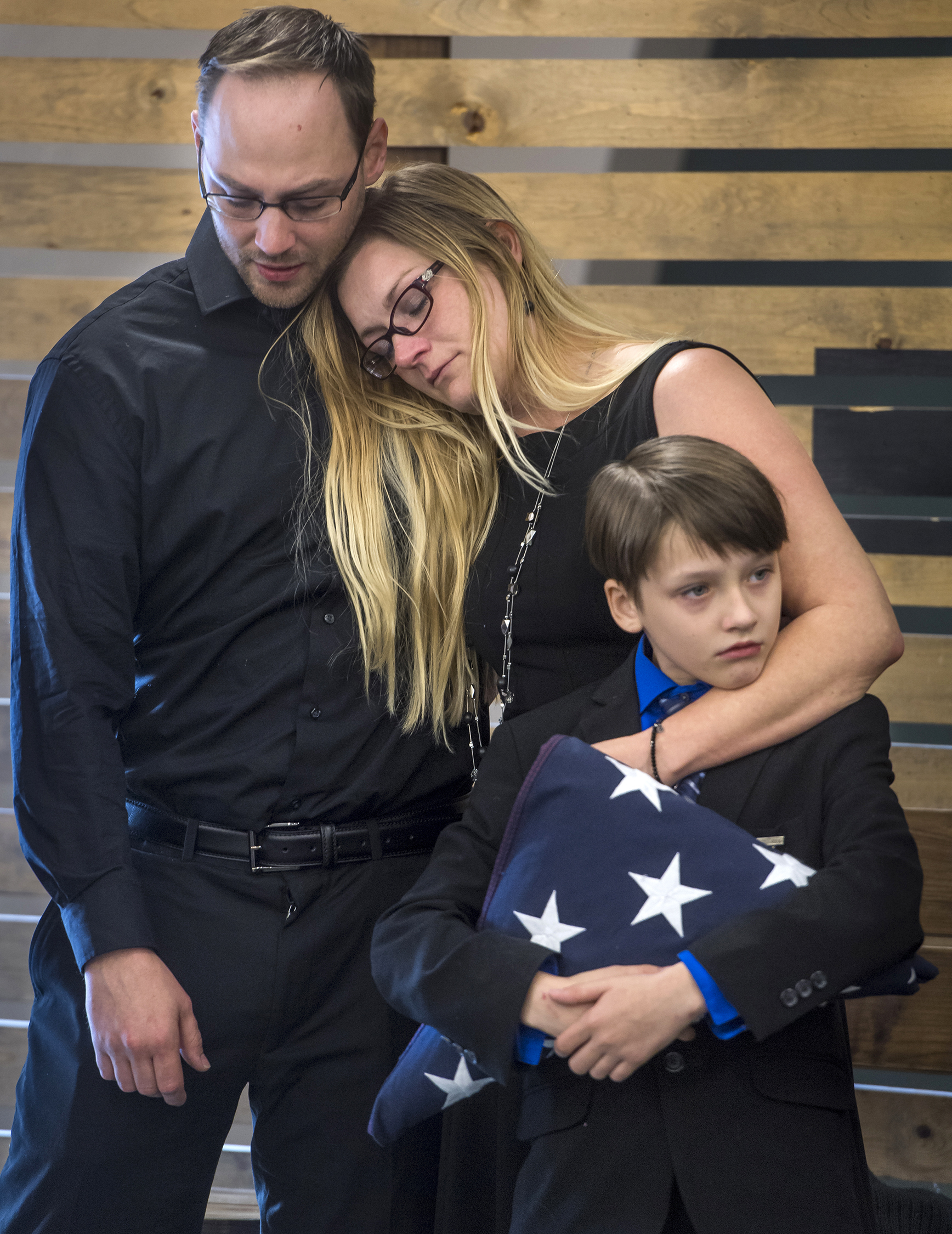 """Mason Robinson, 11, holds the flag presented to him by Marines at the memorial service for his dad and two sisters who died in a house fire last week in rural Tennessee. Mason and his mom Elizabeth """"Angel"""" Robinson, pictured, escaped the blaze. They are with Robinson's brother Jeremy Ward at a memorial service in Santa Ana on Wednesday, Dec  20, 2017."""