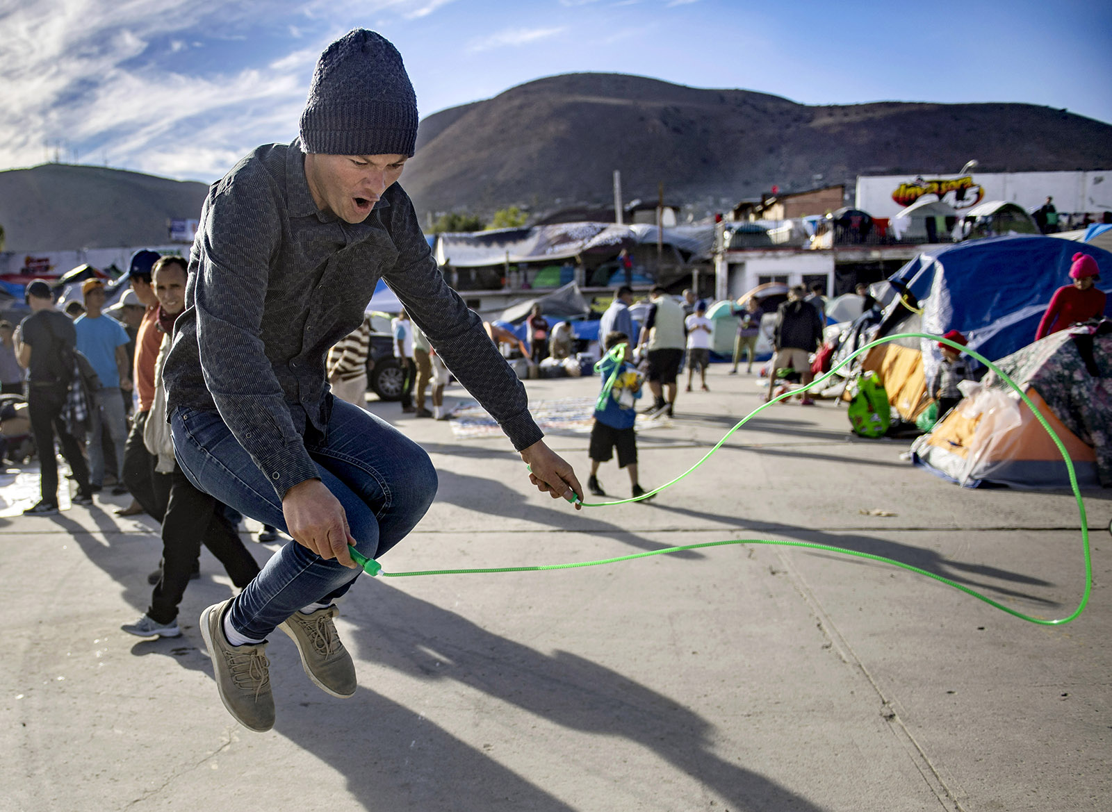 A man puts his new jump rope to use outside the El Barretal shelter after volunteers passed out toys and coloring books in Tijuana on Tuesday, December 4, 2018.