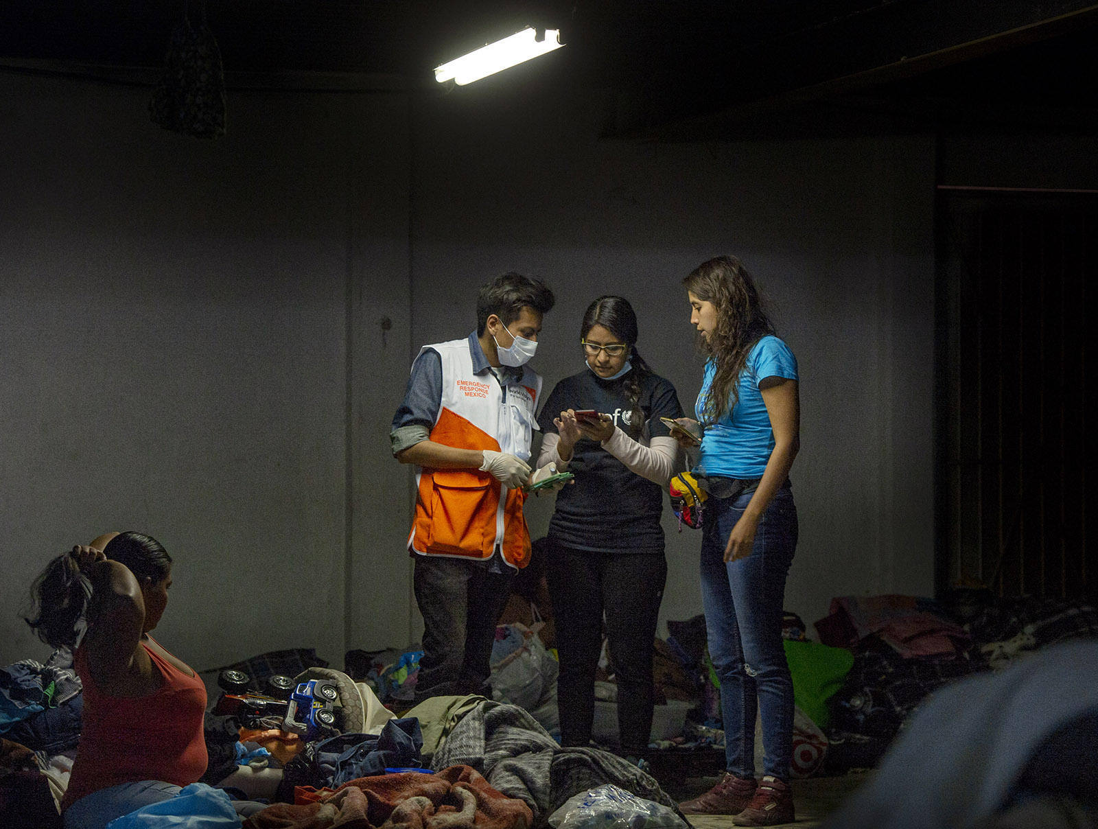 Workers with Unicef, World Vision and La Jugarreta, gather information about the welfare of children staying at the El Barretal shelter in Tijuana on Tuesday, December 4, 2018.