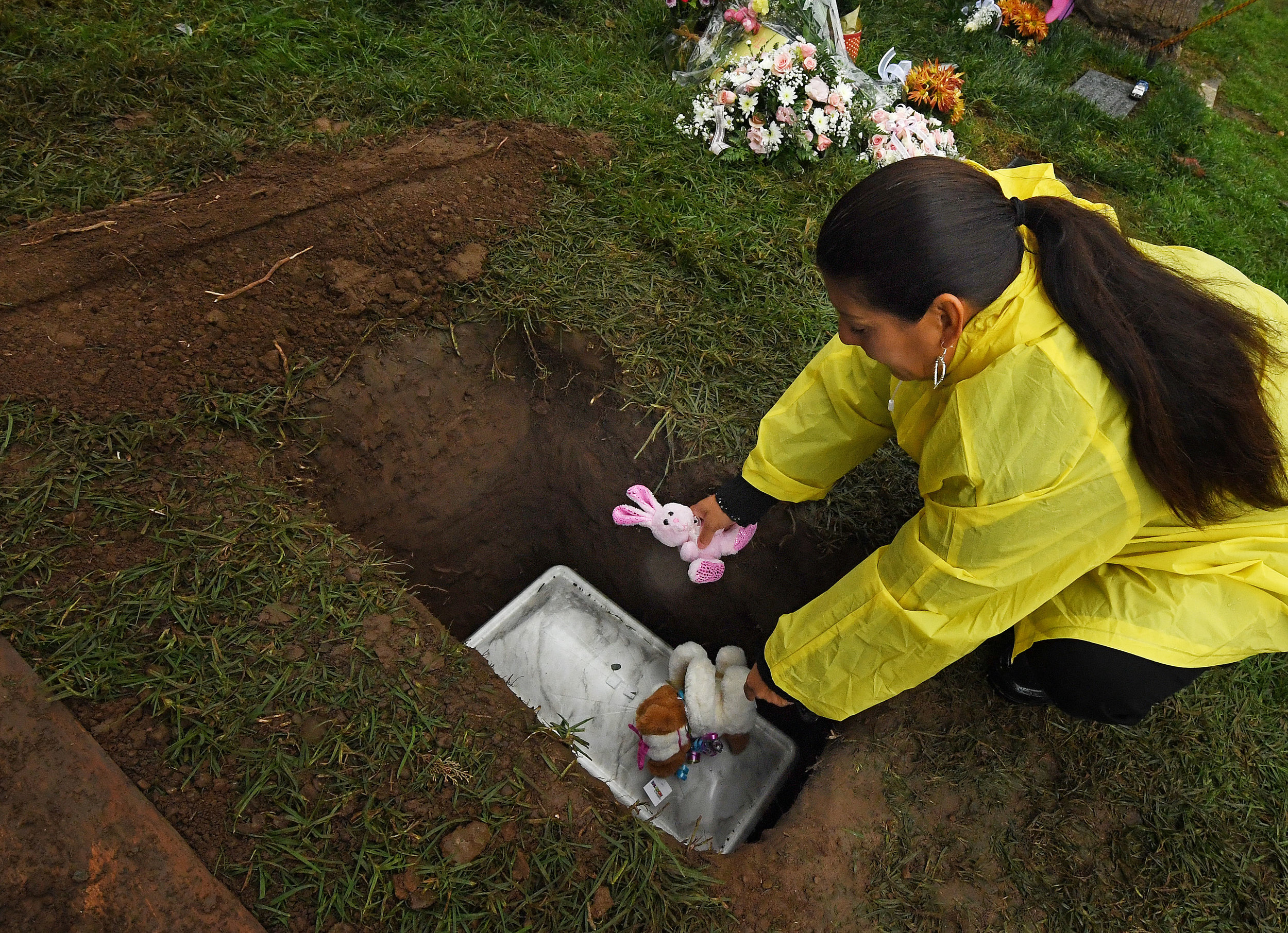 Monica Montejano, from Corona, places stuffed animals atop the grave of Baby Jane Doe at Sunnyslope Cemetery in Corona, Thursday, December 6, 2018. The newborn infant was found in a cardboard box near the 15 freeway in Corona in July. Corona police and fire departments along with others contributed to make the funeral possible for the child. Police are still searching for the person or persons responsible.