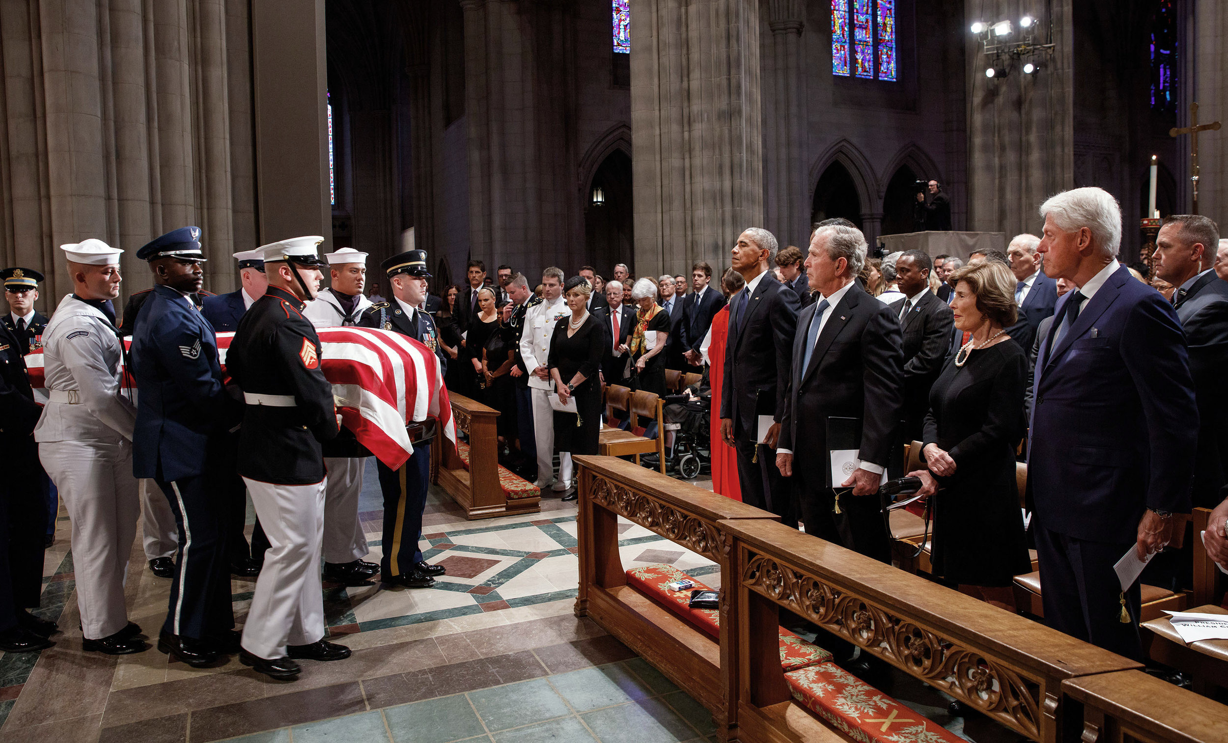Former presidents Barack Obama, George W. Bush, and Bill Clinton watch the casket of Sen. John McCain  leave the National Cathedral in Washington, D.C. The McCain family is gathered on the other side of the aisle.  Obama and Bush, who both ran against McCain in presidential contests and won, were eulogists at his request. President Trump was not invited to attend.